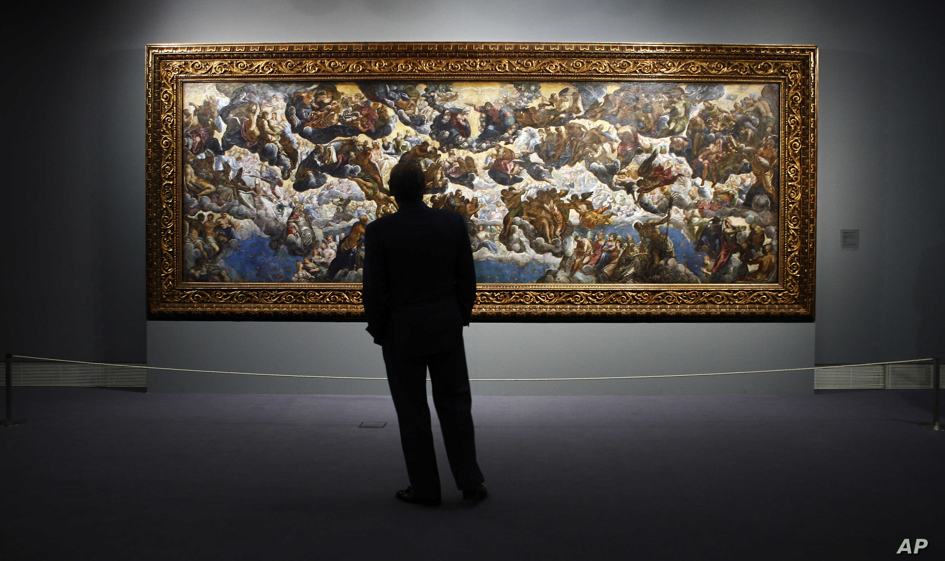 """FILE - A man looks at """"The Coronation of the Virgin, The Paradise"""" a painting by 16th century Venetian artist Tintoretto at the Thyssen-Bornemisza Museum in Madrid, June 7, 2006."""