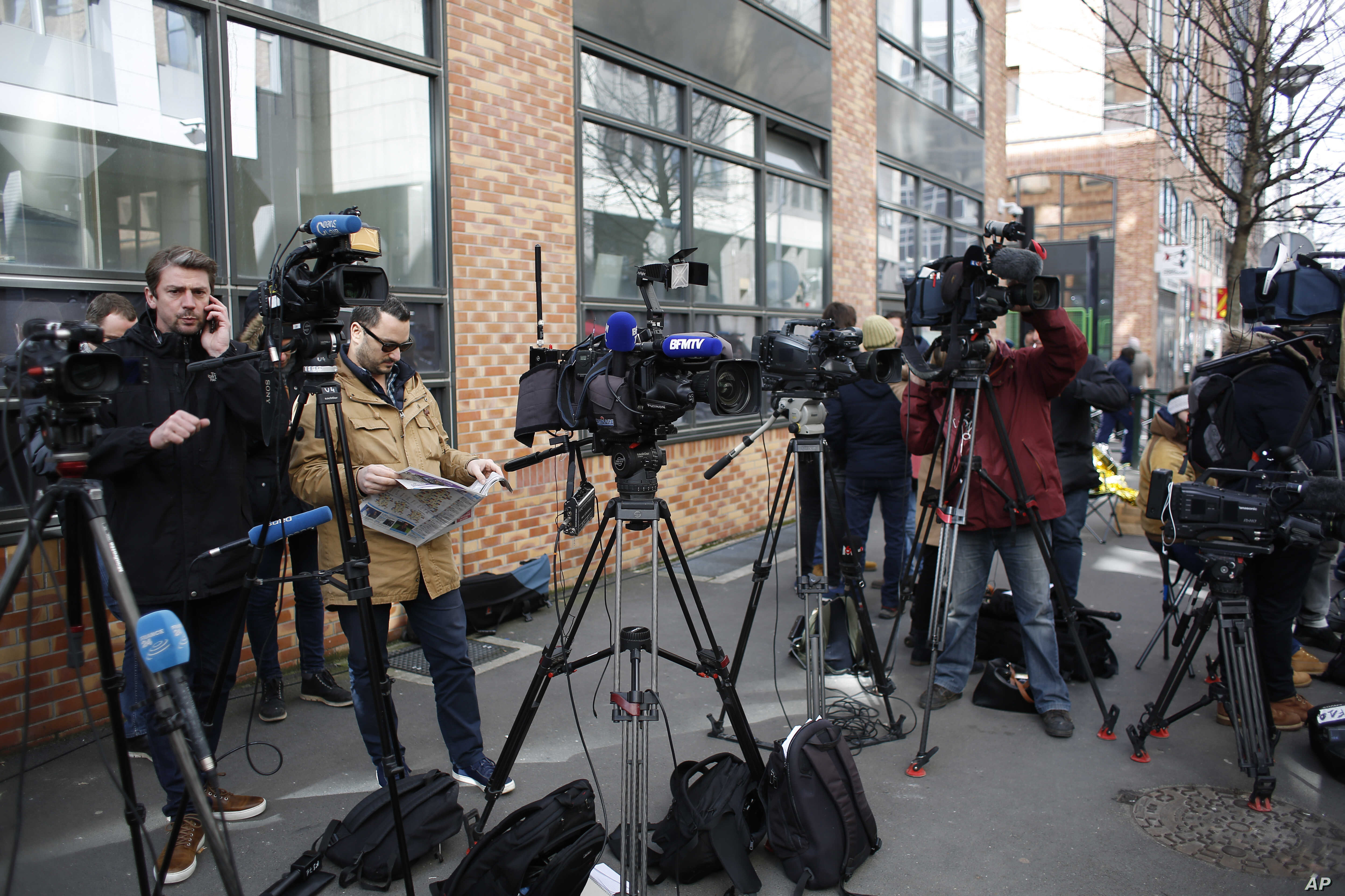 Reporters gather outside the police station where former French President Nicolas Sarkozy was being held in Nanterre, outside Paris, March 21, 2018.