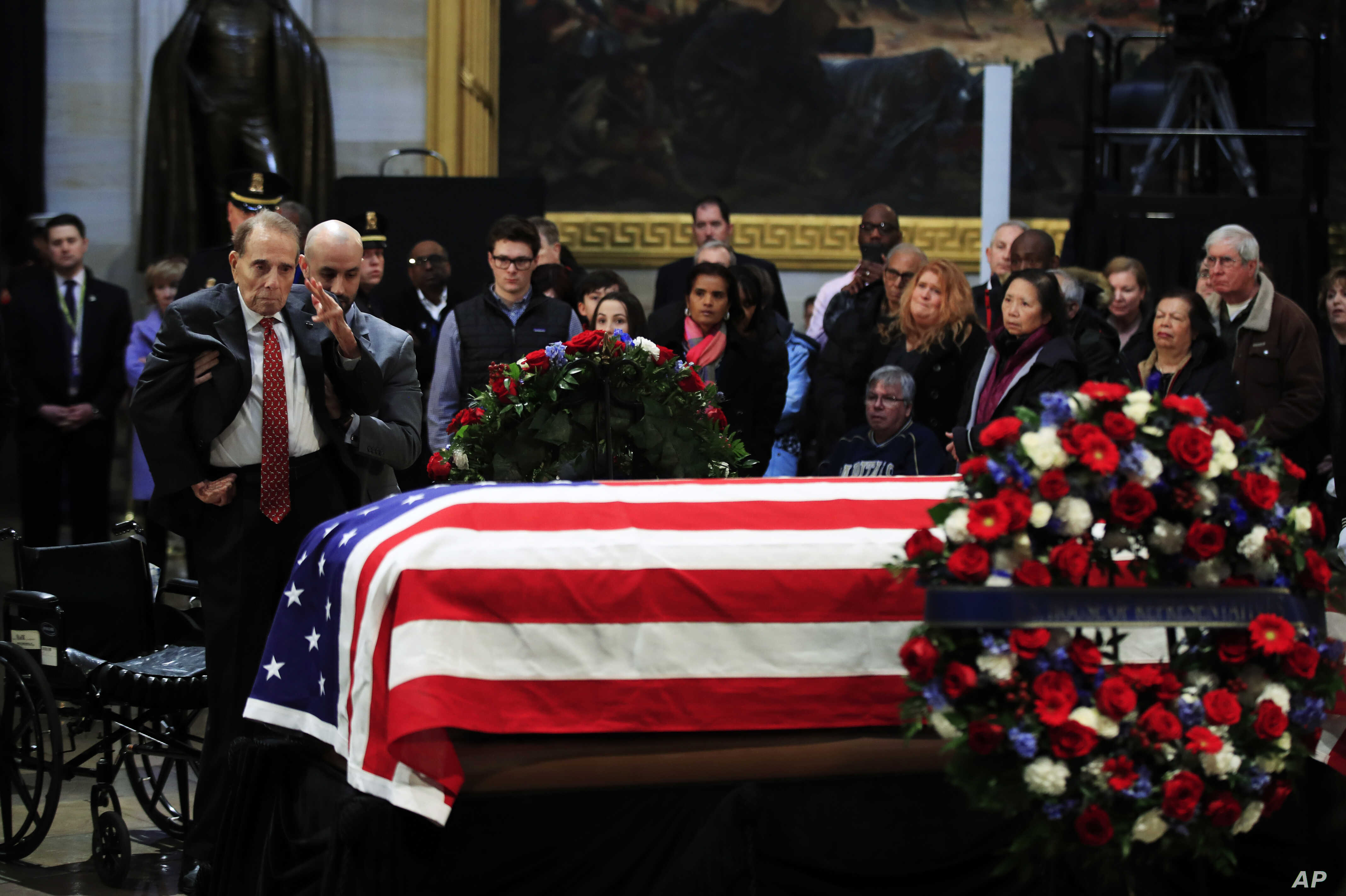 Former Sen. Bob Dole salutes the flag-draped casket containing the remains of former President George H.W. Bush as he lies in state at the U.S. Capitol in Washington,  Dec. 4, 2018.