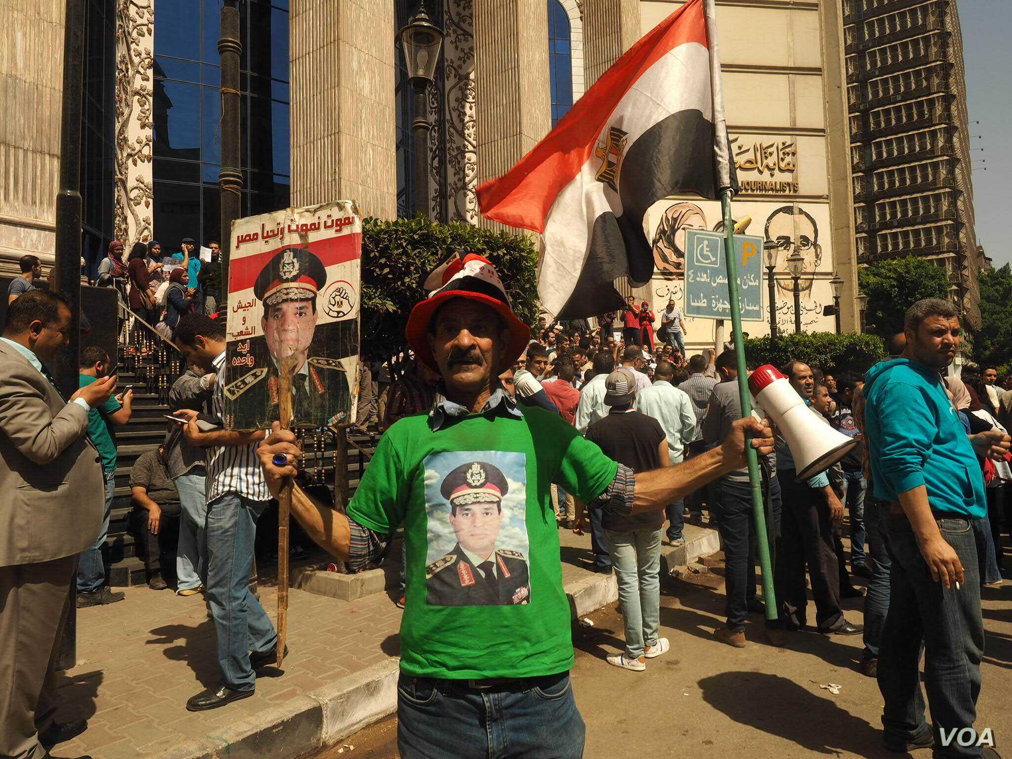 A government supporter holds the Egyptian flag and a poster of President Abdel-Fattah el-Sissi at a mostly anti-government protest in downtown Cairo, April 15, 2016. (VOA/H. Elrasam)