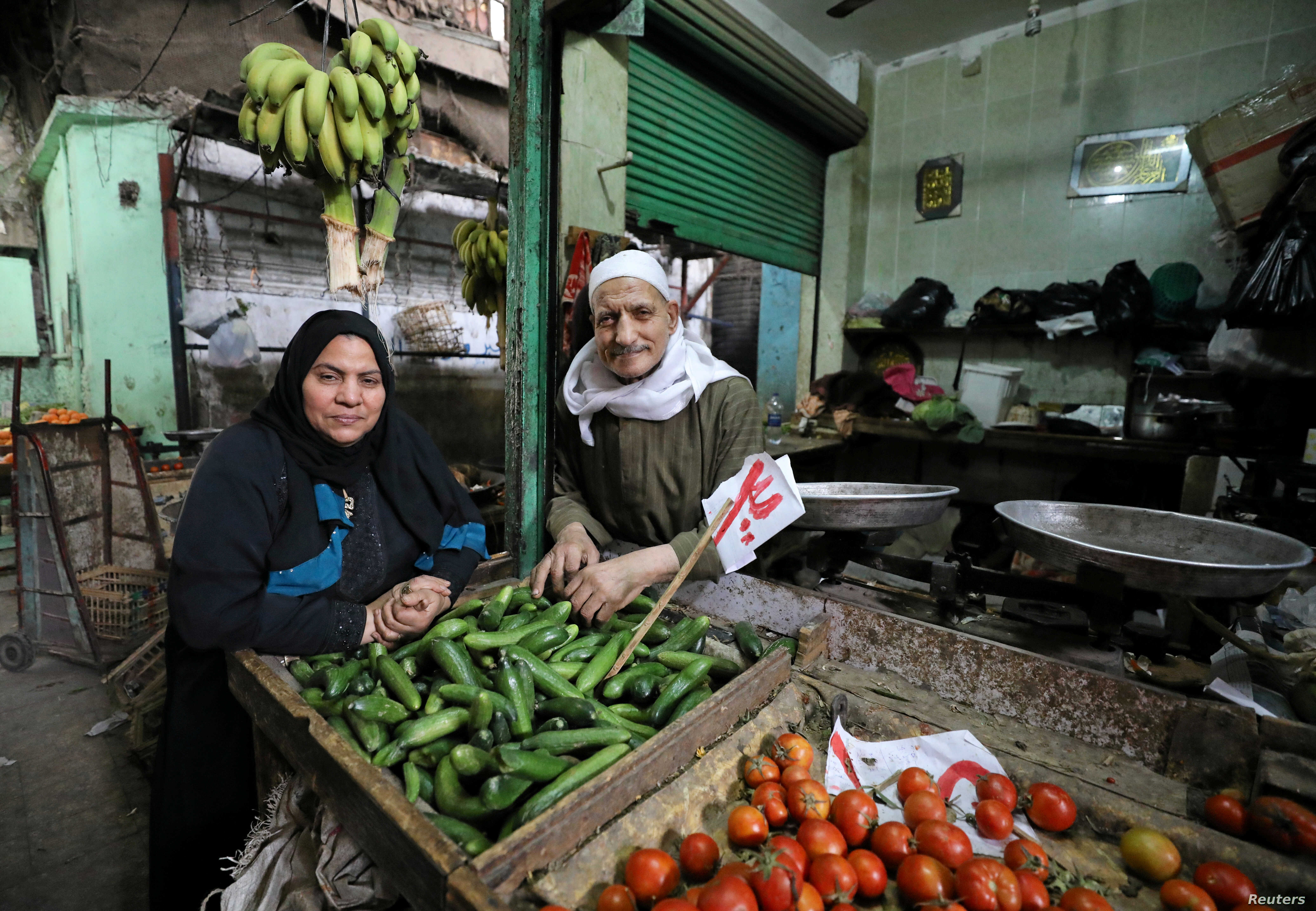 Hayes Mehana (R), 78, and Om Hany, 60, pose for a photograph at a vegetable market in Cairo, Egypt, February 12, 2018.