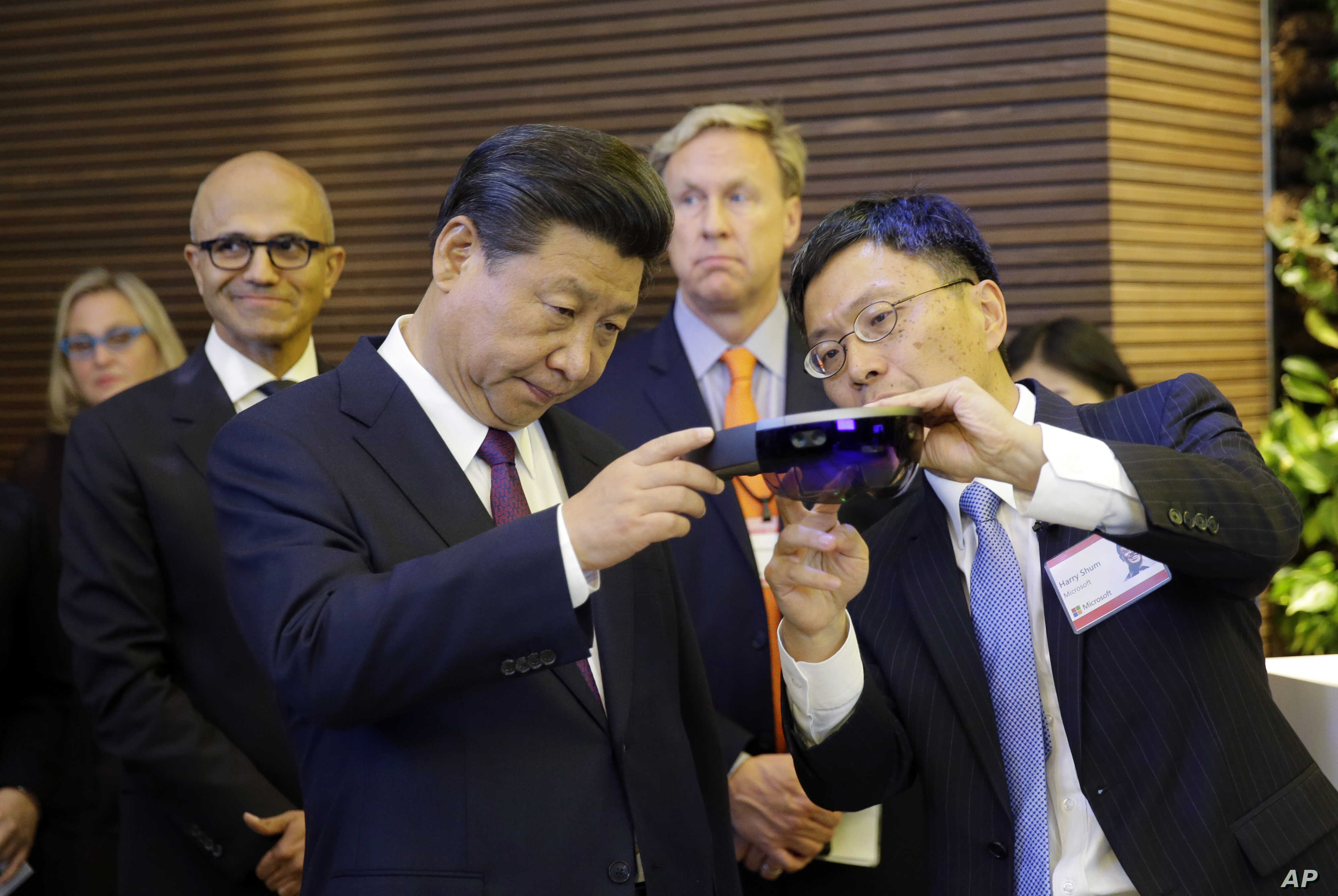 Harry Shum, right, Microsoft Executive Vice President of Technology and Research, demonstrates Micosoft's HoloLens device to Chinese President Xi Jinping, left, during a tour of Microsoft's main campus in Redmond, Wash., Wednesday, Sept. 23, 2015.