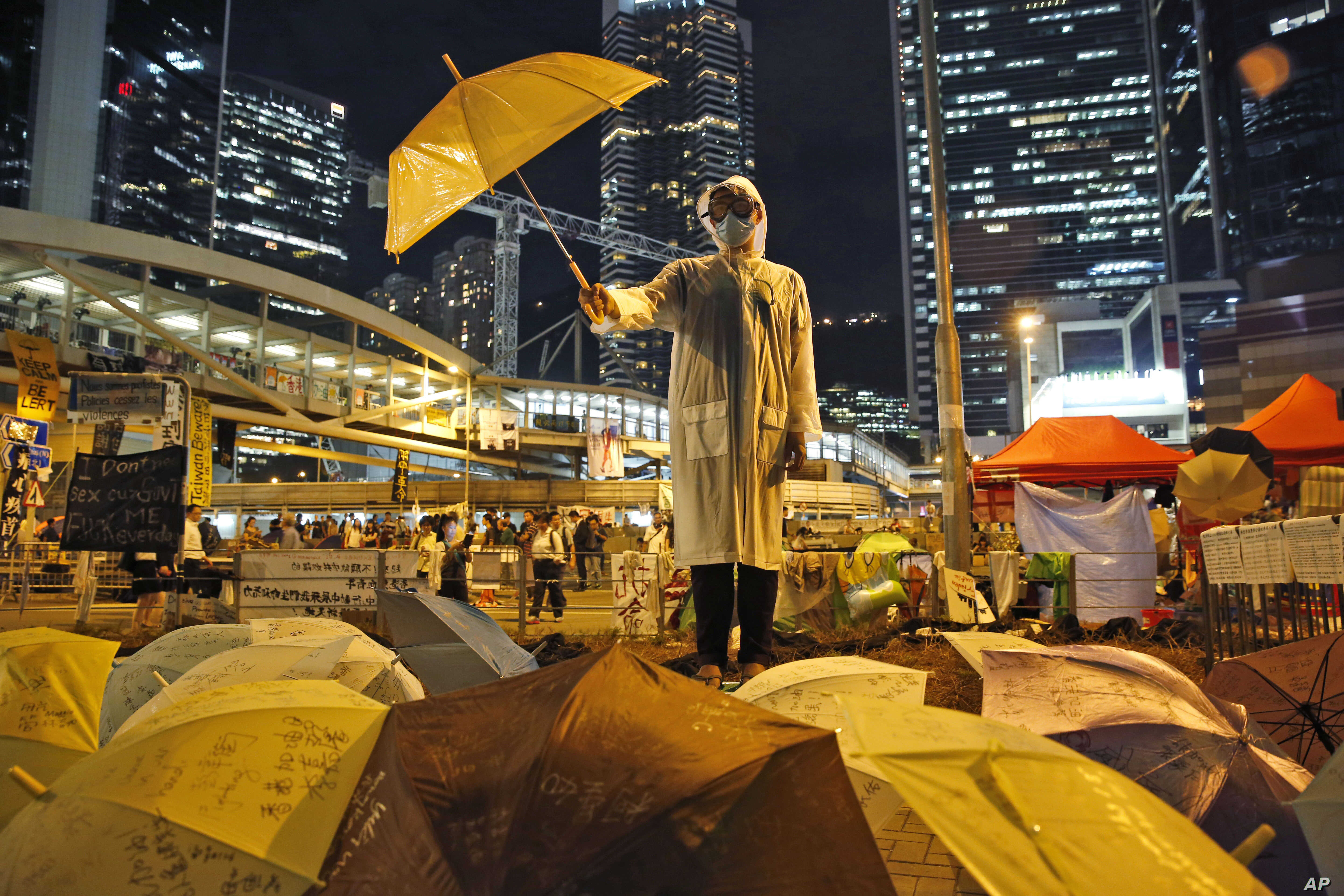 A protester holds an umbrella during a performance on a main road in the occupied areas outside government headquarters in Hong Kong's Admiralty in Hong Kong, Oct. 9, 2014.
