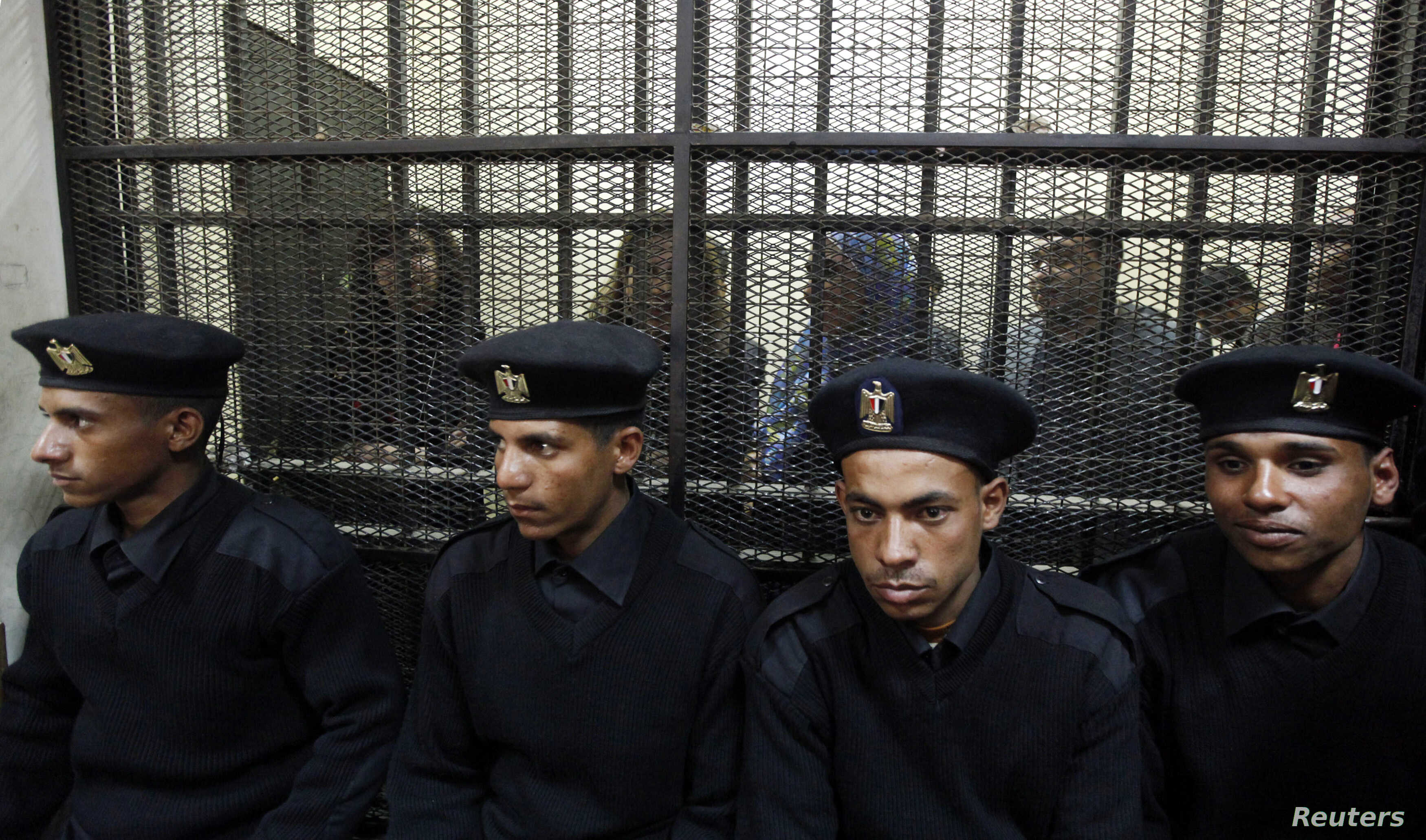 FILE - Some of the 14 Egyptian activists who were accused of working for unlicensed nongovernmental organizations (NGOs) and receiving illegal foreign funds stand in a cage during the opening of their trial in Cairo, Feb. 26, 2012.