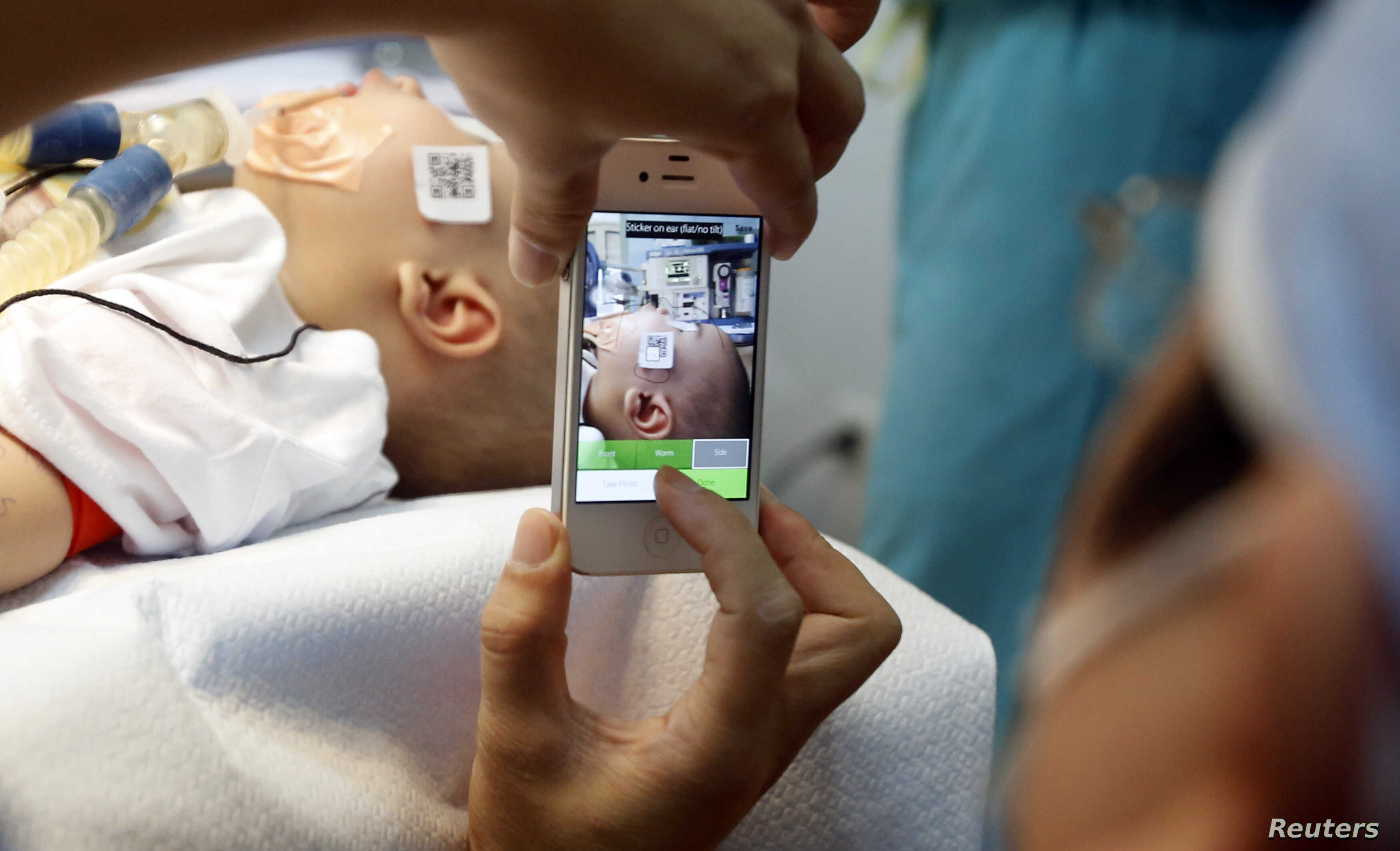 A doctor uses a smartphone to take a photo of a child with facial deformity before surgery at the Vietnam Cuba hospital in Hanoi, Nov. 18, 2014.