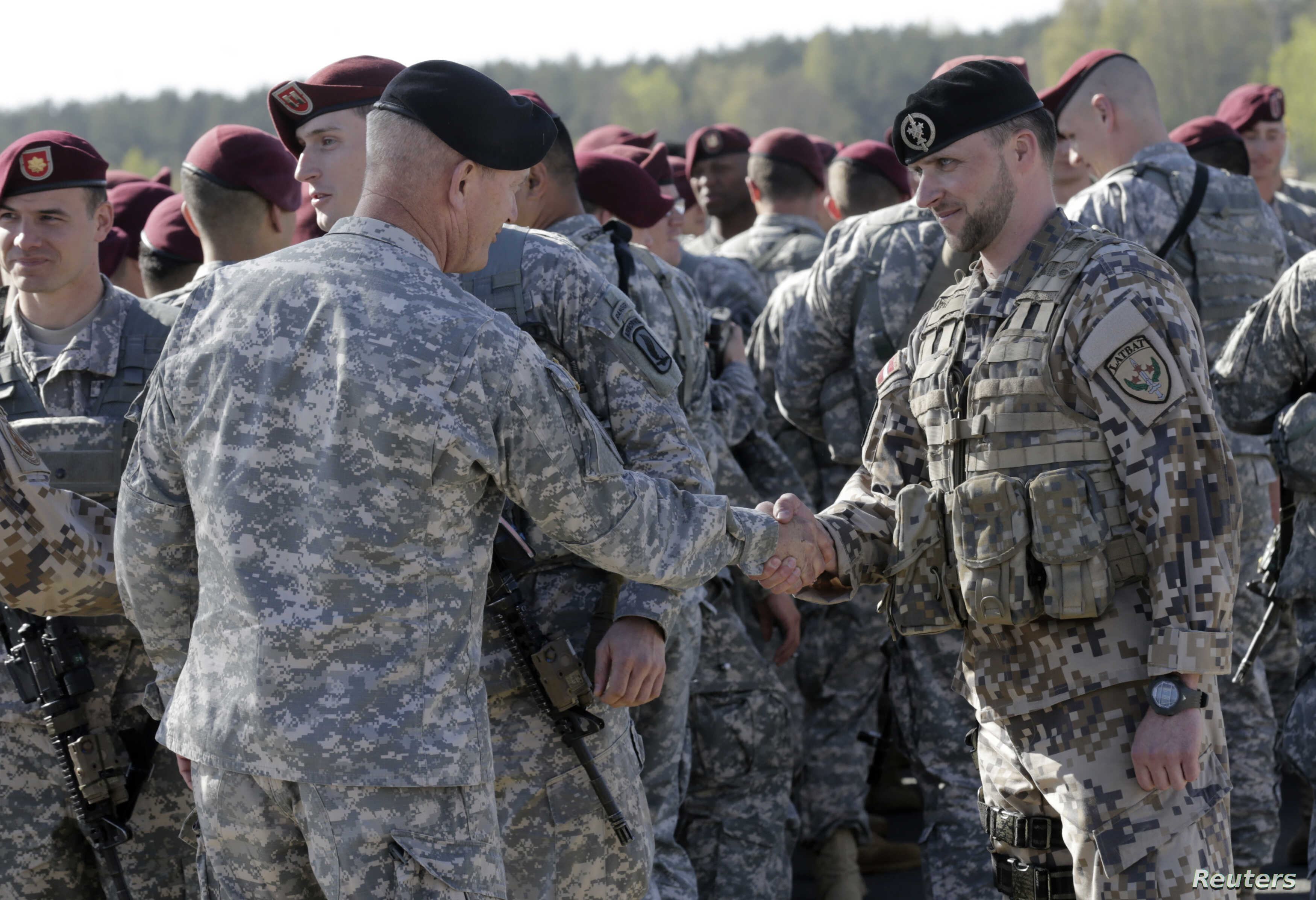 A Latvian army officer (R) shakes hands with his U.S. counterpart as a contingent of U.S. Army paratroopers arrive at the airport in Riga April 24, 2014.