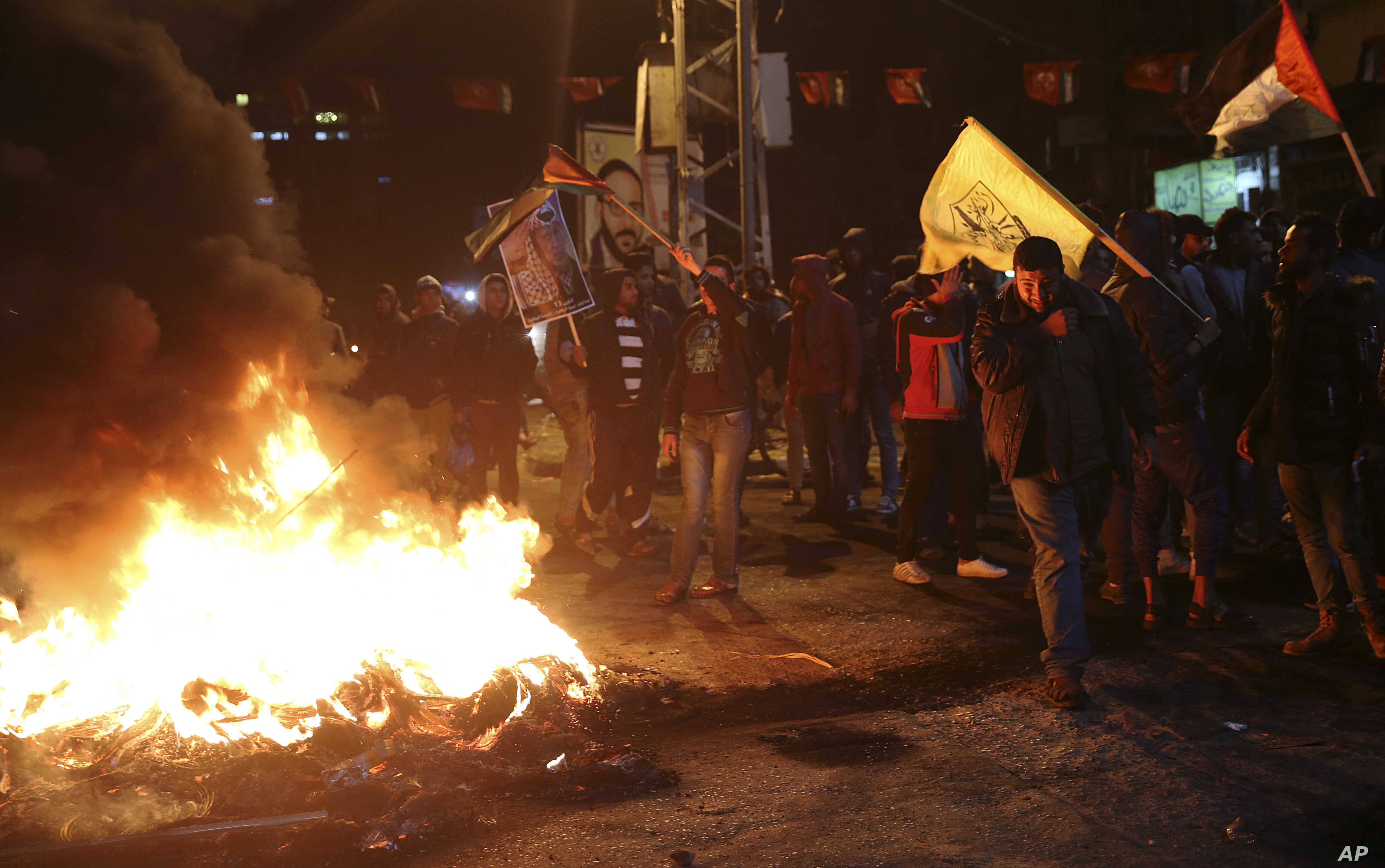 Palestinian protesters burn tires as they wave Palestinian flags and pictures of late Palestinian president Yasser Arafat during a protest in Gaza City, Dec. 6, 2017. Defying worldwide warnings, U.S. President Donald Trump on Wednesday broke with dec...