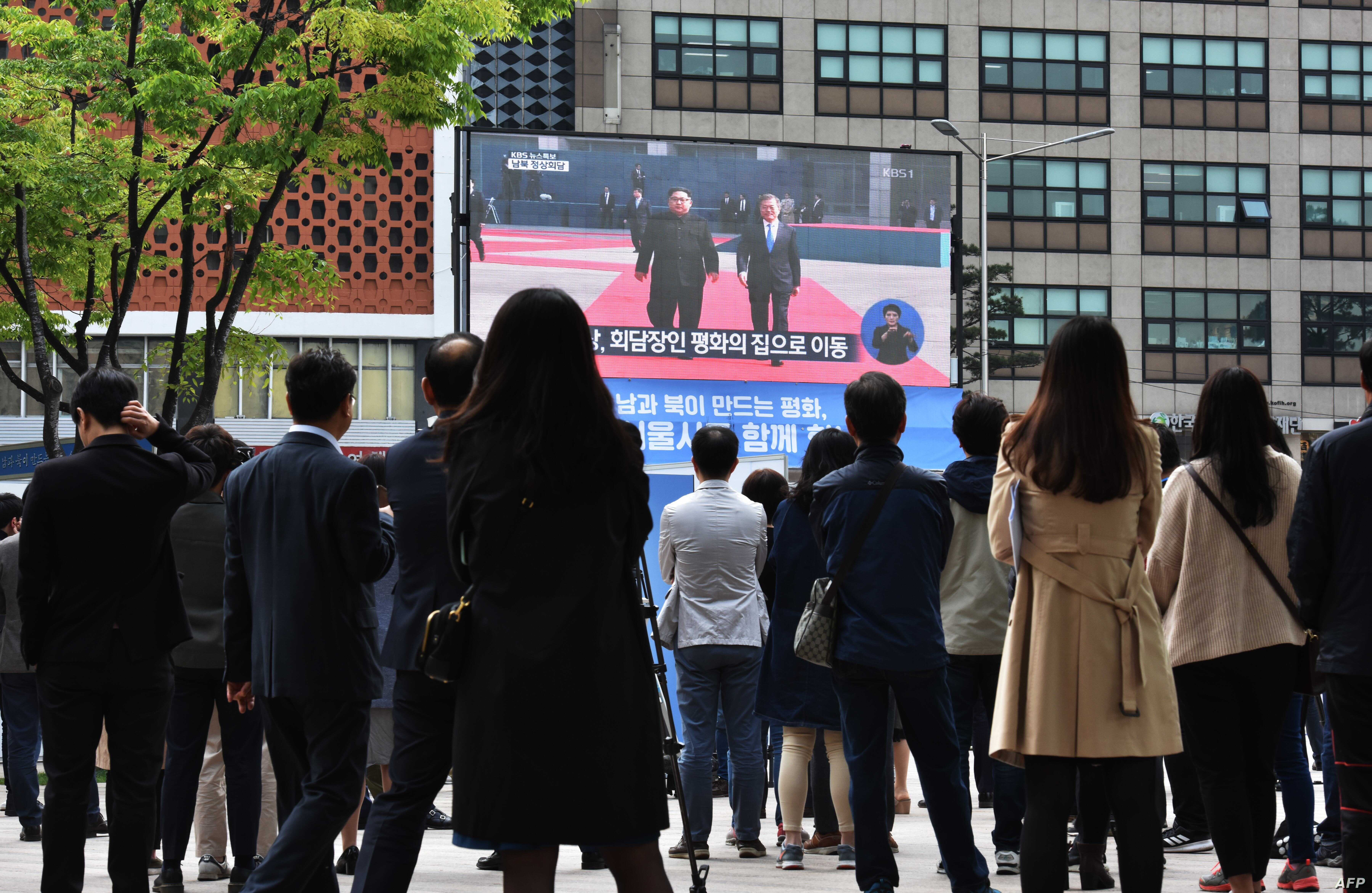 People watch live footage of South Korean President Moon Jae-in (R) walking with North Korean leader Kim Jong Un (L) at the Demilitarized Zone, on a screen in Seoul on April 27, 2018.