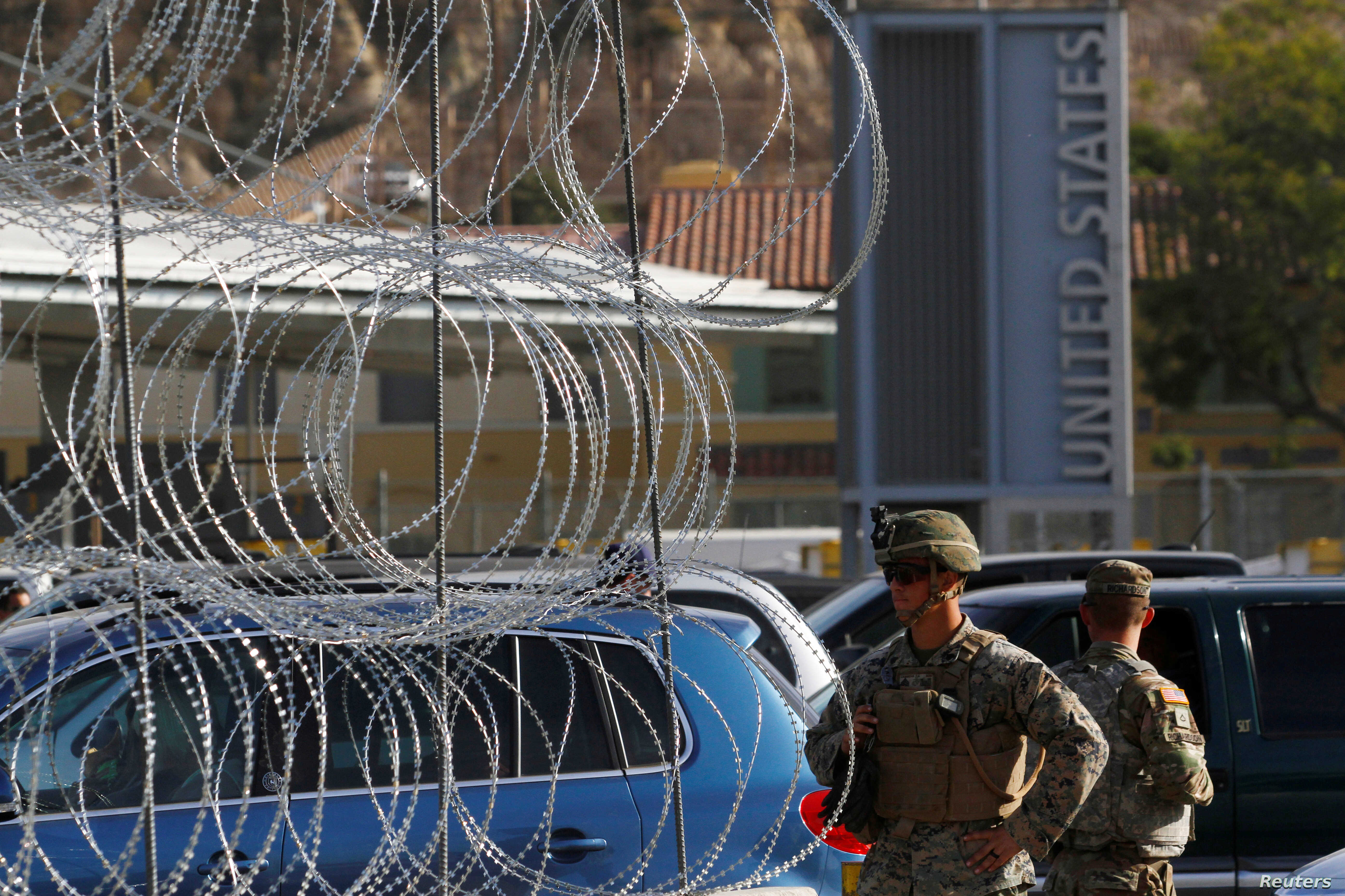 U.S. Marines stand guard next to a barricade with concertina wire at the border between Mexico and the U.S., in preparation for the arrival of migrants, in Tijuana, Mexico, Nov. 13, 2018.