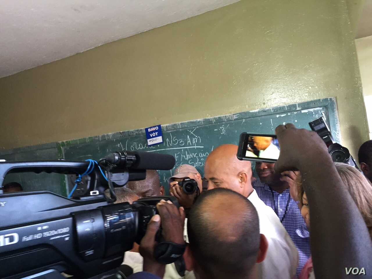 Haiti's President Michel Martelly on his way to vote at a polling station in Petion-Ville, Haiti, Oct. 25, 2015. (J. Belizaire/VOA)