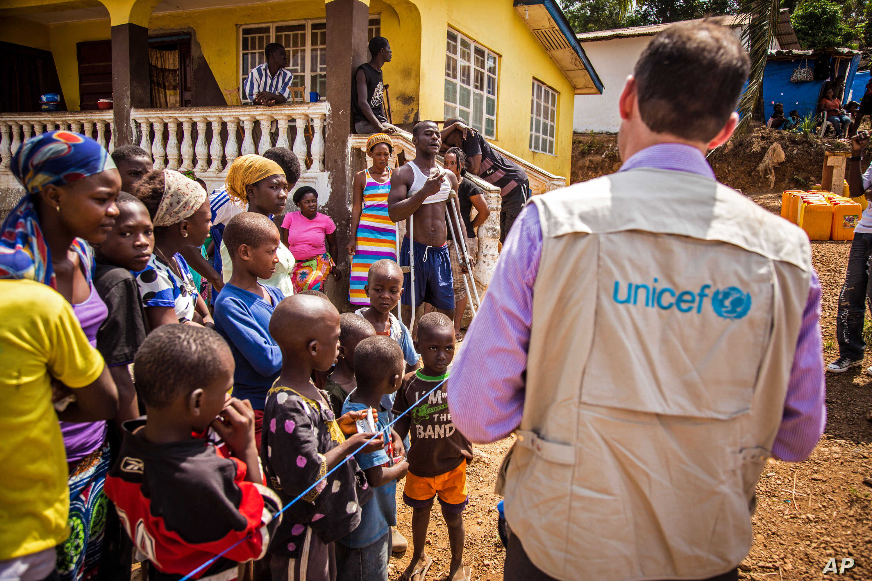 A UNICEF aid worker visits a home in Freetown, Sierra Leone, that has been quarantined for 21 days because of the Ebola virus, Feb. 26,  2015.