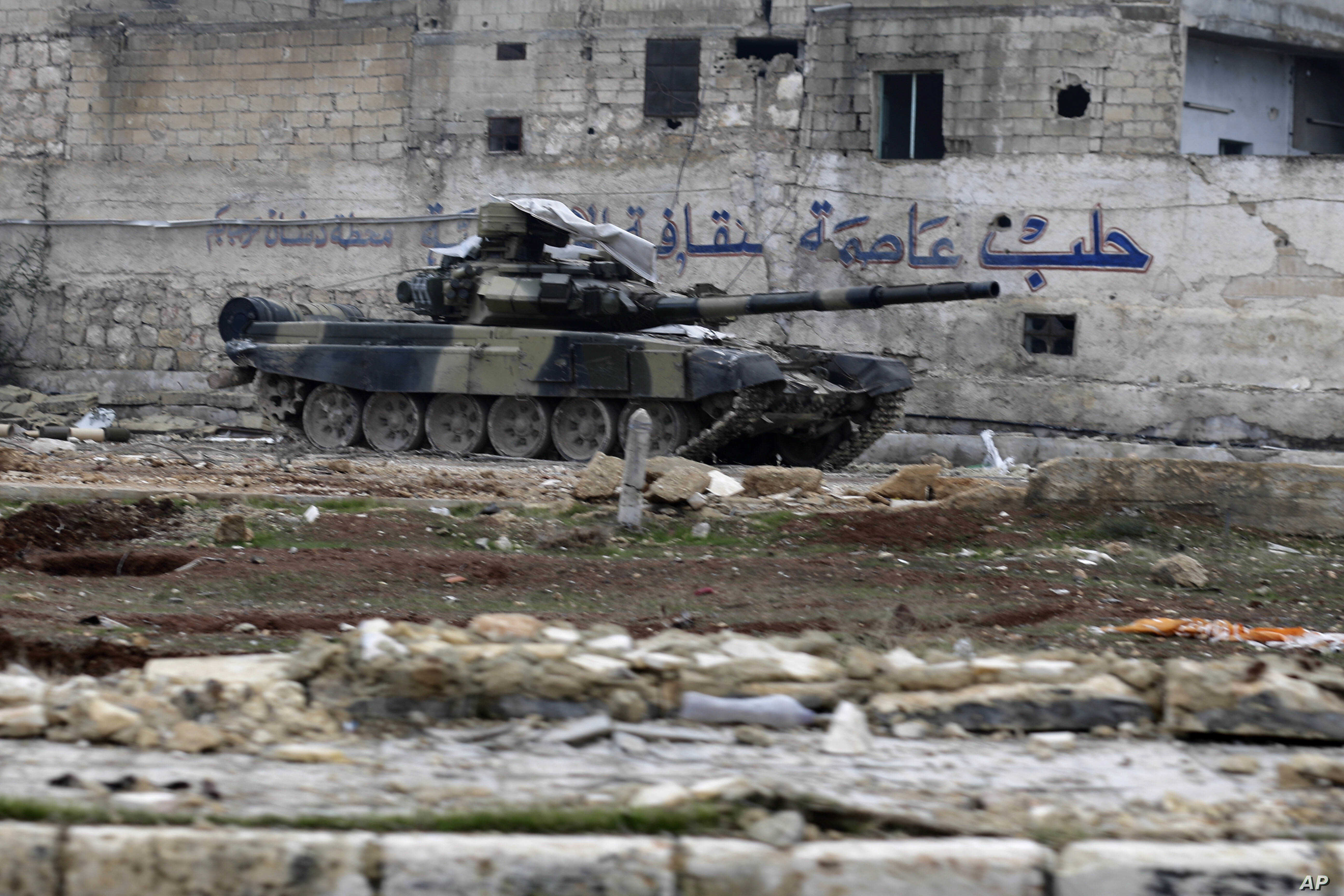 """A Syrian army tank is seen in front of a wall with Arabic that reads """"Aleppo is the capital of culture"""" in the east Aleppo neighborhood of Tariq al-Bab, Syria, Dec. 3, 2016."""