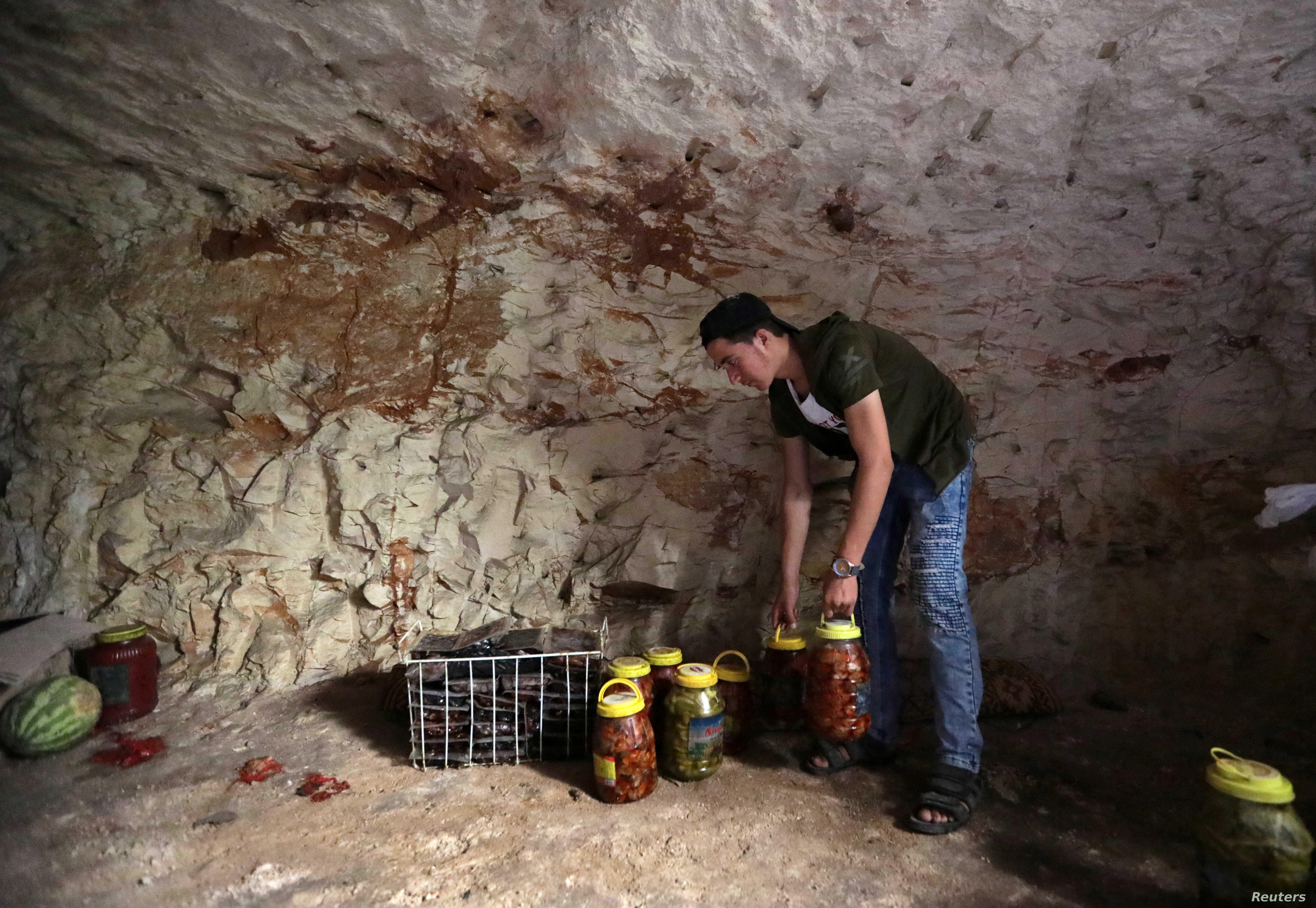 A man holds pickled vegetables in an underground cave in Idlib, Syria, Sept. 3, 2018. The city is bracing for an attack by Syrian forces.