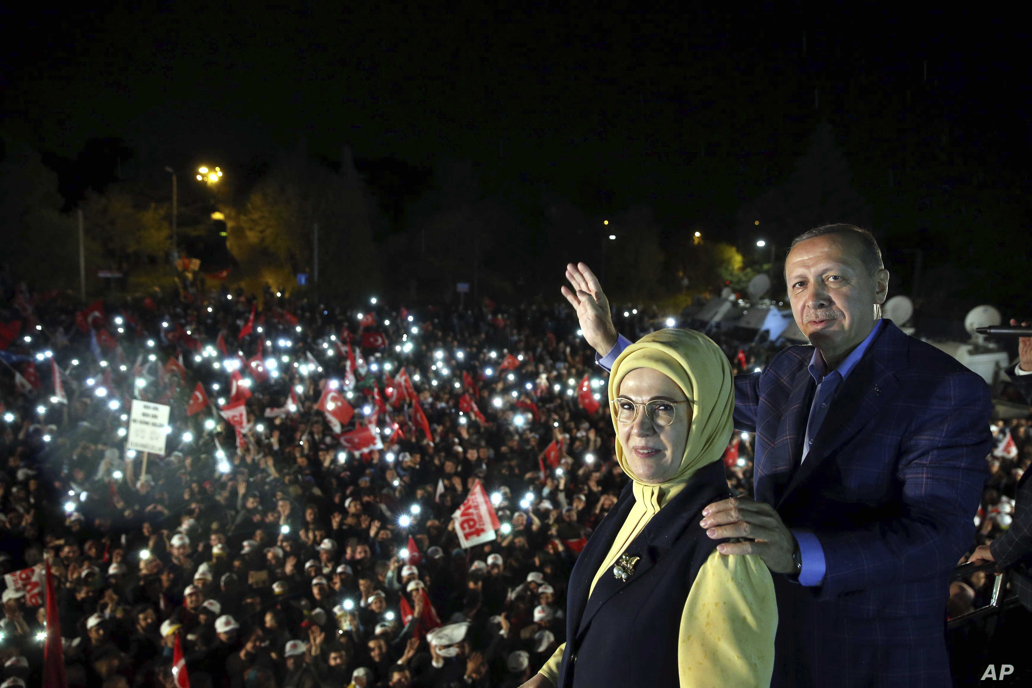 Turkey's President Recep Tayyip Erdogan and his wife Emine Erdogan pose for photos with cheering supporters in the background after unofficial referendum results were announced, in Istanbul, late Sunday, April 16, 2017.
