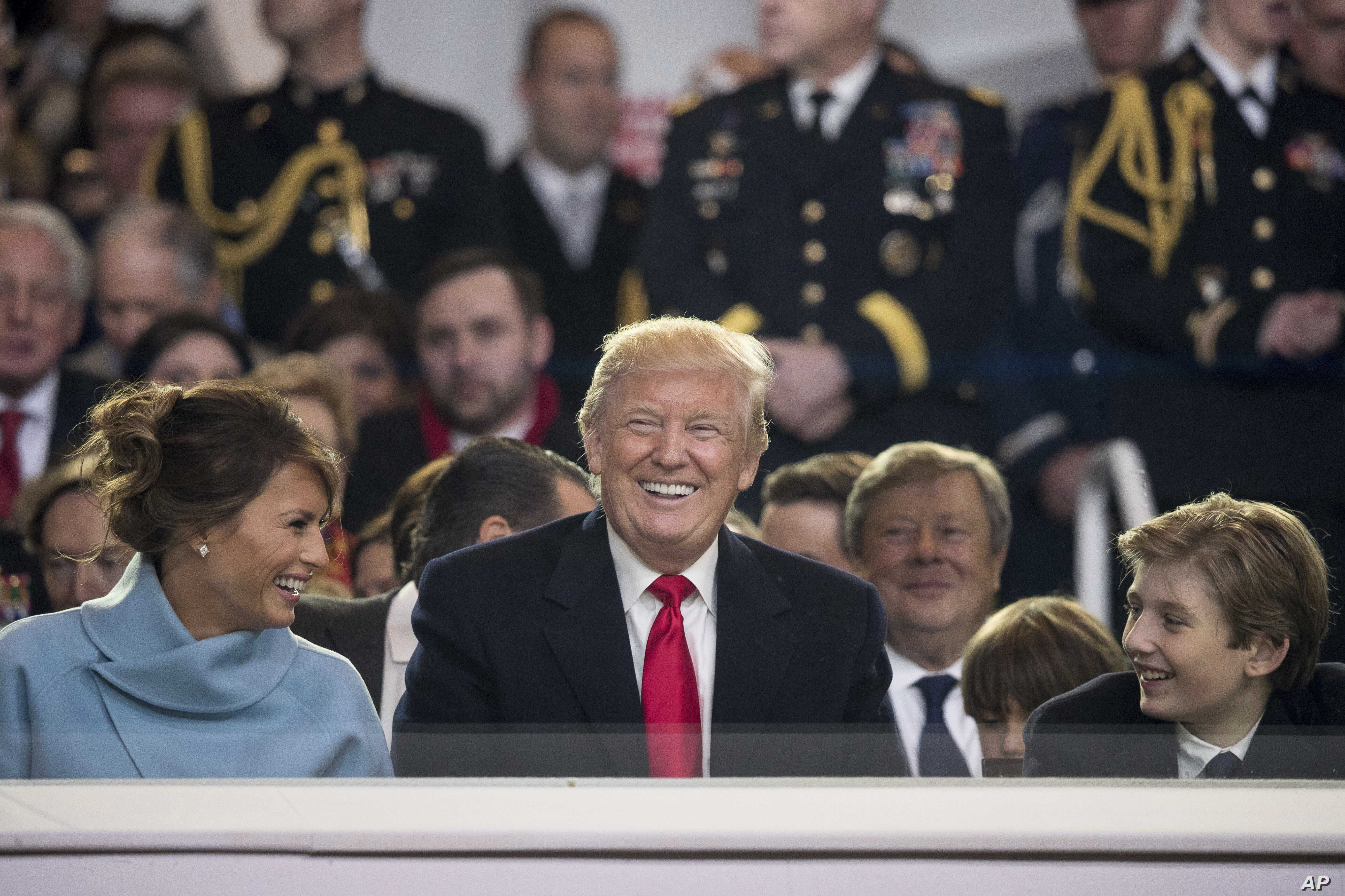 President Donald Trump shares a laugh with first lady Melania Trump and son Barron Trump as they sit in the reviewing stand during Trump's inaugural parade on Pennsylvania Avenue outside the White House in Washington, Jan. 20, 2017.