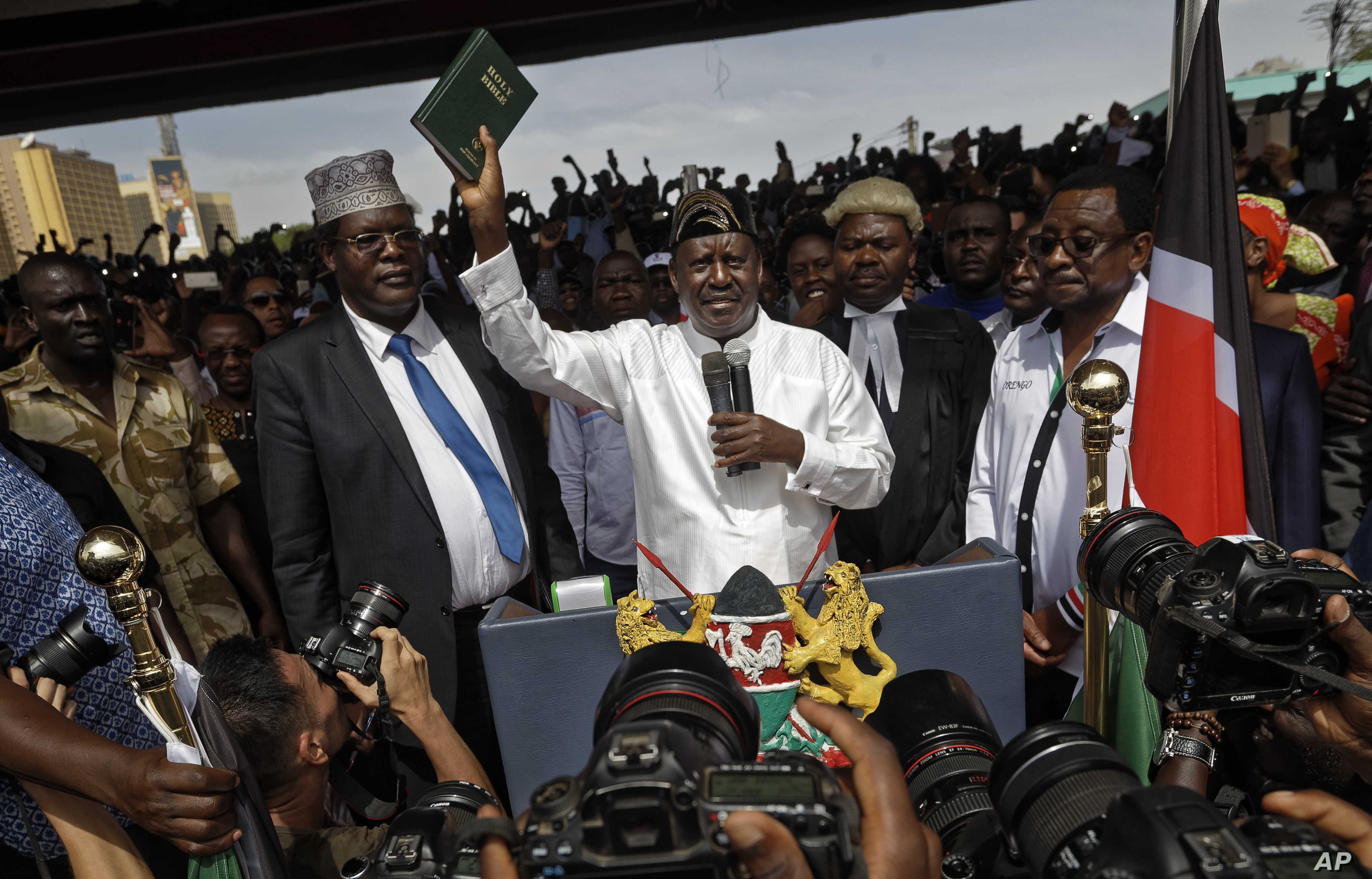 """FILE - Opposition leader Raila Odinga (C) accompanied by lawyers Miguna Miguna (C-L), Tom """"T.J."""" Kajwang, (C-R) and politician James Orengo (R) holds a bible aloft after swearing an oath during a mock """"swearing-in"""" ceremony at Uhuru Park in downtown ..."""