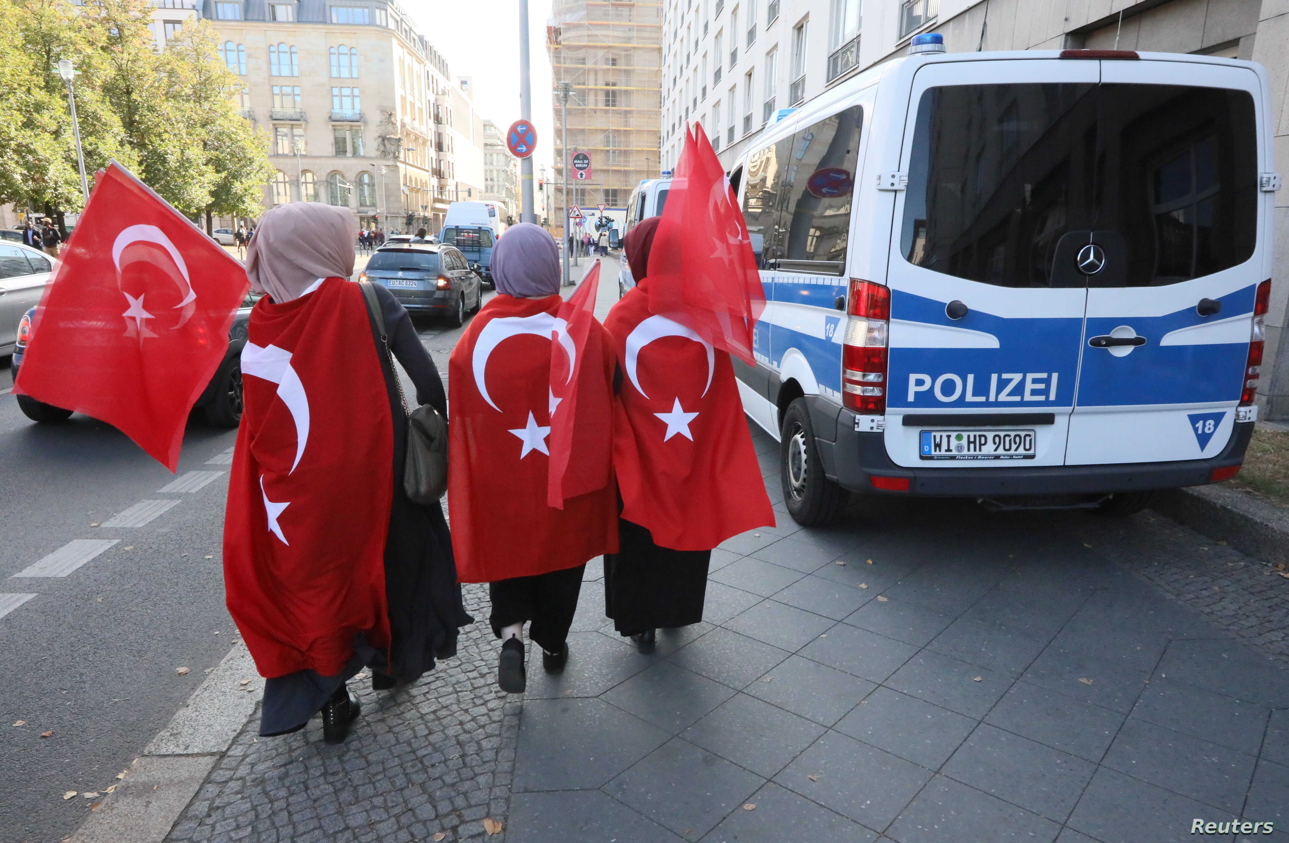 Supporters of Turkish President Recep Tayyip Erdogan walk along the security zone around the Adlon Hotel in Berlin, Sept. 27, 2018.