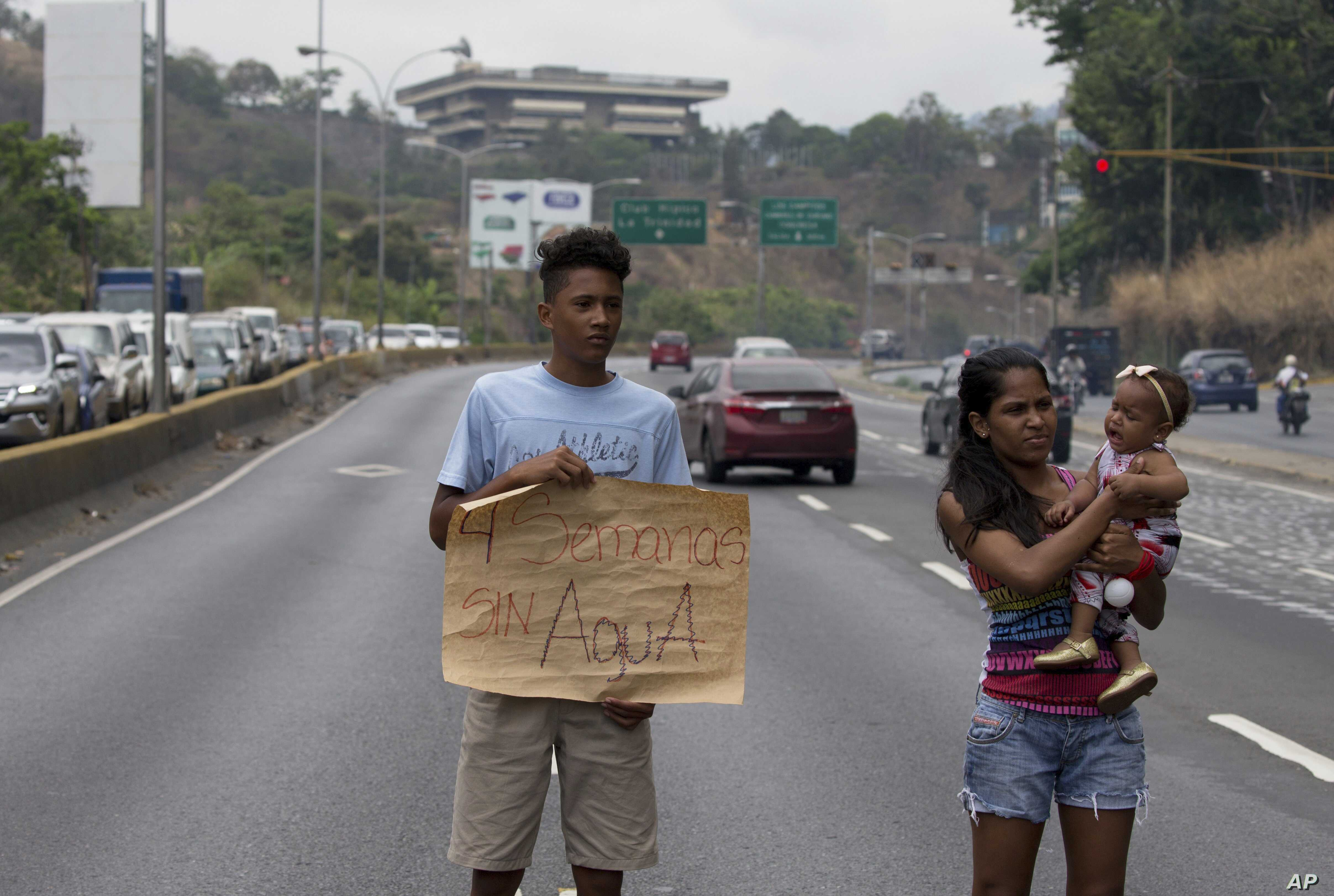 """FILE - A demonstrator from Las Minitas shantytown holds up a poster that reads in Spanish """"Four weeks without water"""" after water service was suspended, on the Prados del Este highway in the Santa Fe neighborhood of Caracas, Venezuela, April 27, 2018...."""