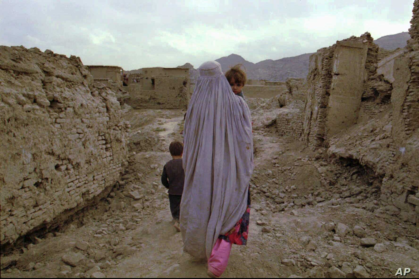 FILE - A widow carries her child home through a destroyed neighborhood in Kabul, Oct. 9, 1996.