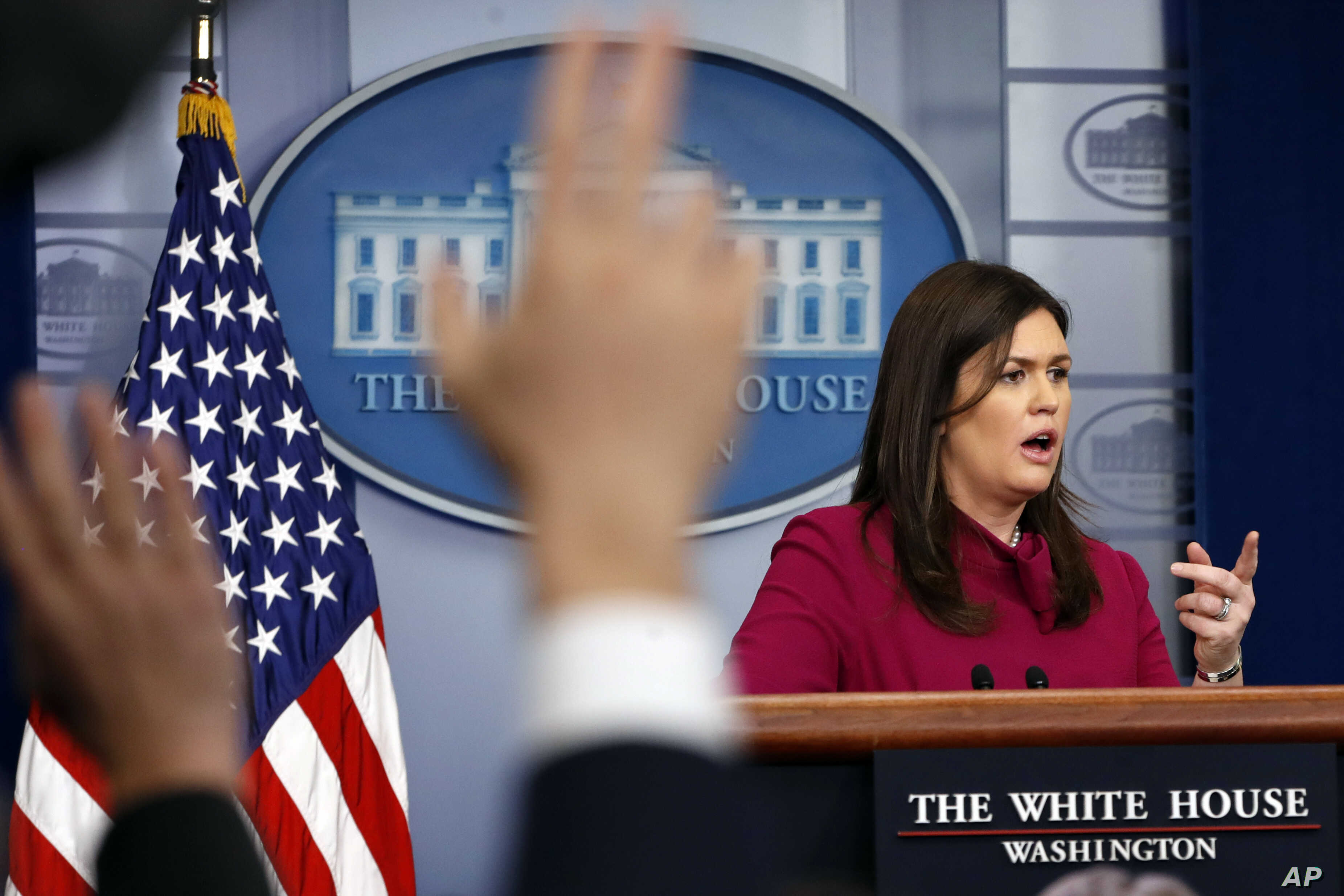 White House press secretary Sarah Huckabee Sanders answers a question as reporters raise their hands during the daily news briefing at the White House, Feb. 20, 2018, in Washington.