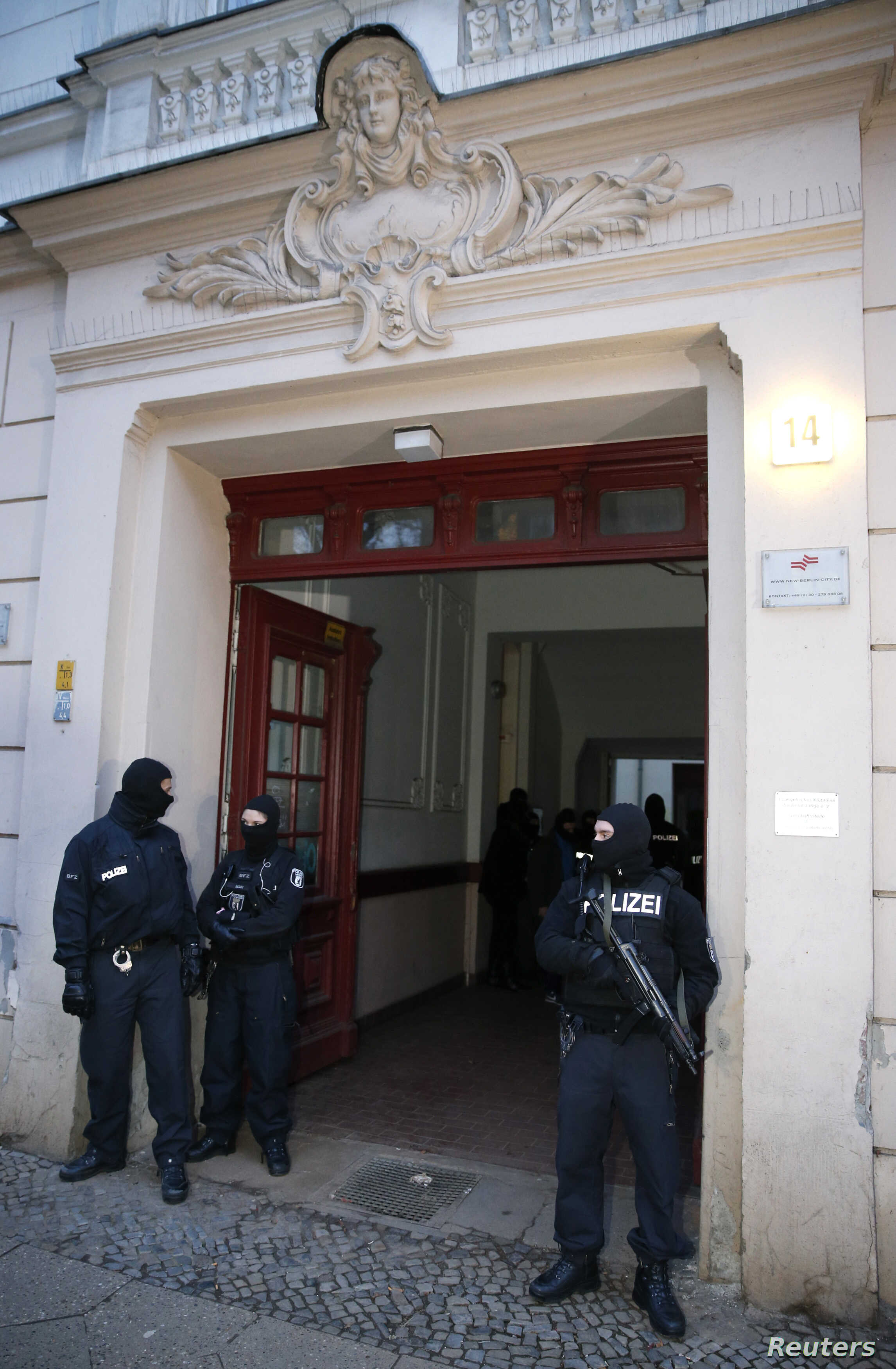 German special police units guard an entrance of an apartment building in the Wedding district in Berlin January 16, 2015. Around 250 policemen took part in the raid and arrested two suspected Islamists, police said.  REUTERS/Fabrizio Bensch (GERMANY...