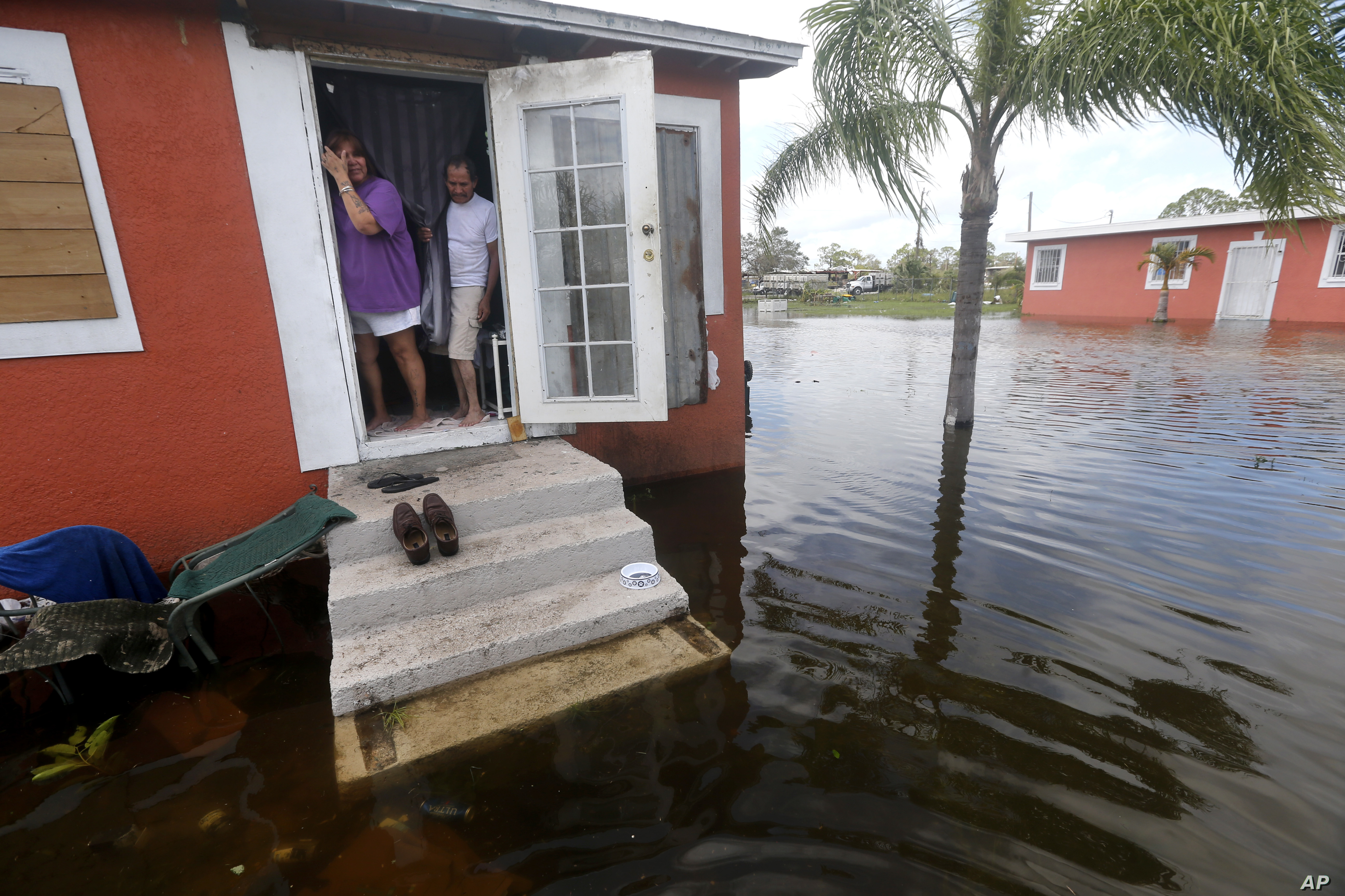 Quintana and Liz Perez look at the flooding outside their home in the aftermath of Hurricane Irma, Sept. 11, 2017, in Immokalee, Fla.