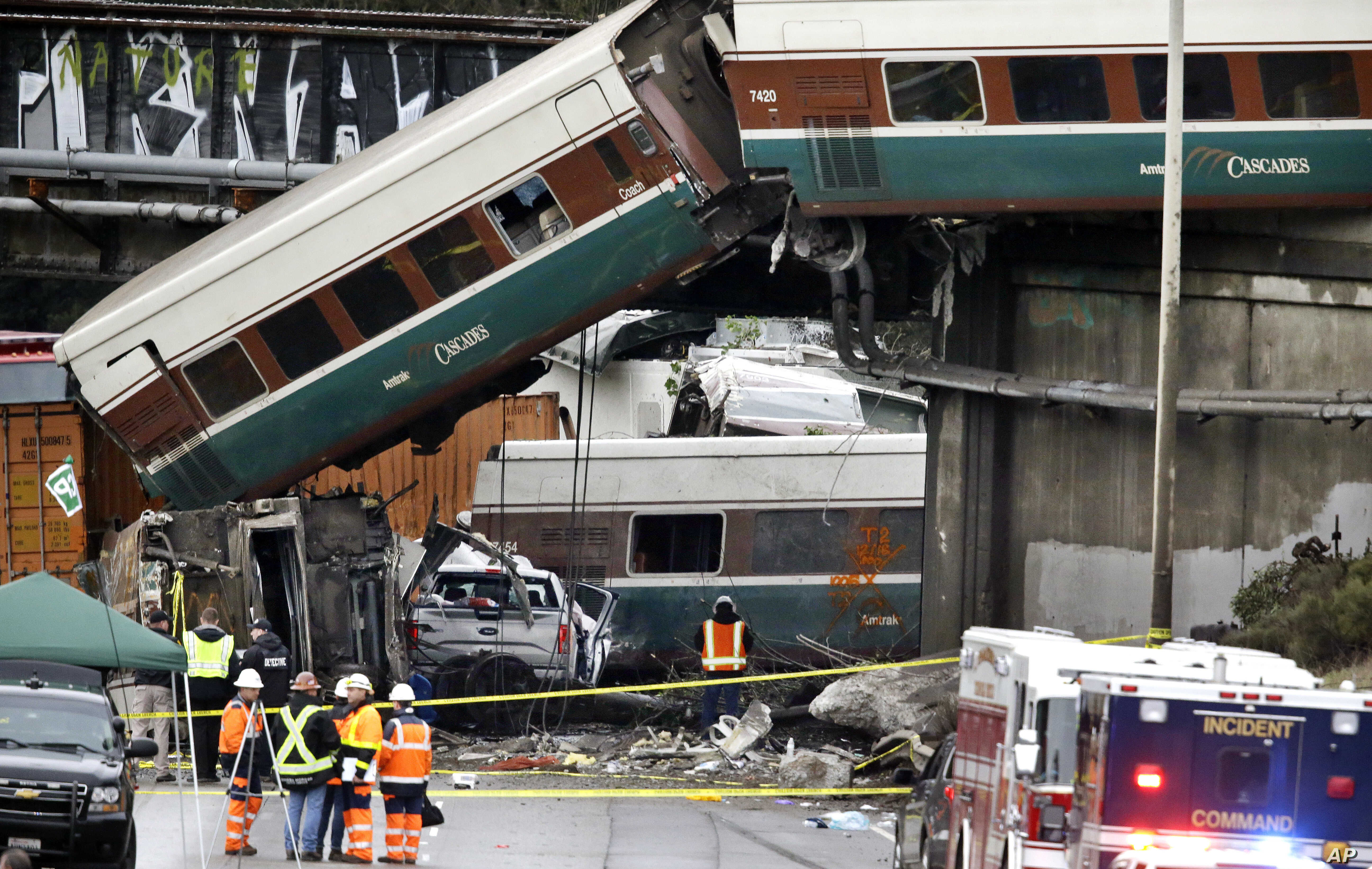 Cars from an Amtrak train lay spilled onto Interstate 5 below alongside smashed vehicles as some train cars remain on the tracks above, Dec. 18, 2017, in DuPont, Wash.