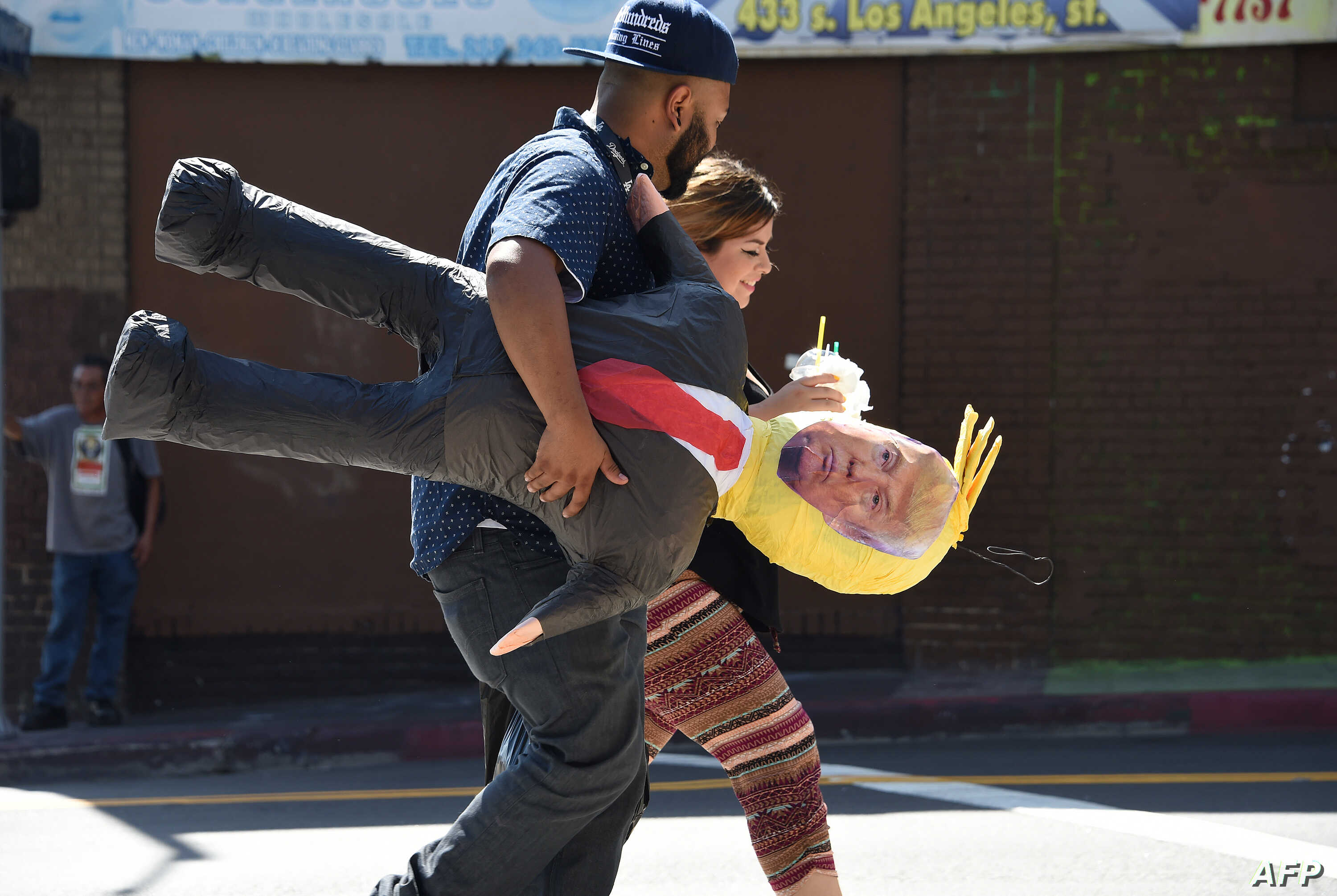 A Latino couple walk with a pinata of Republican presidential candidate Donald Trump, September 23, 2015 in downtown Los Angeles.
