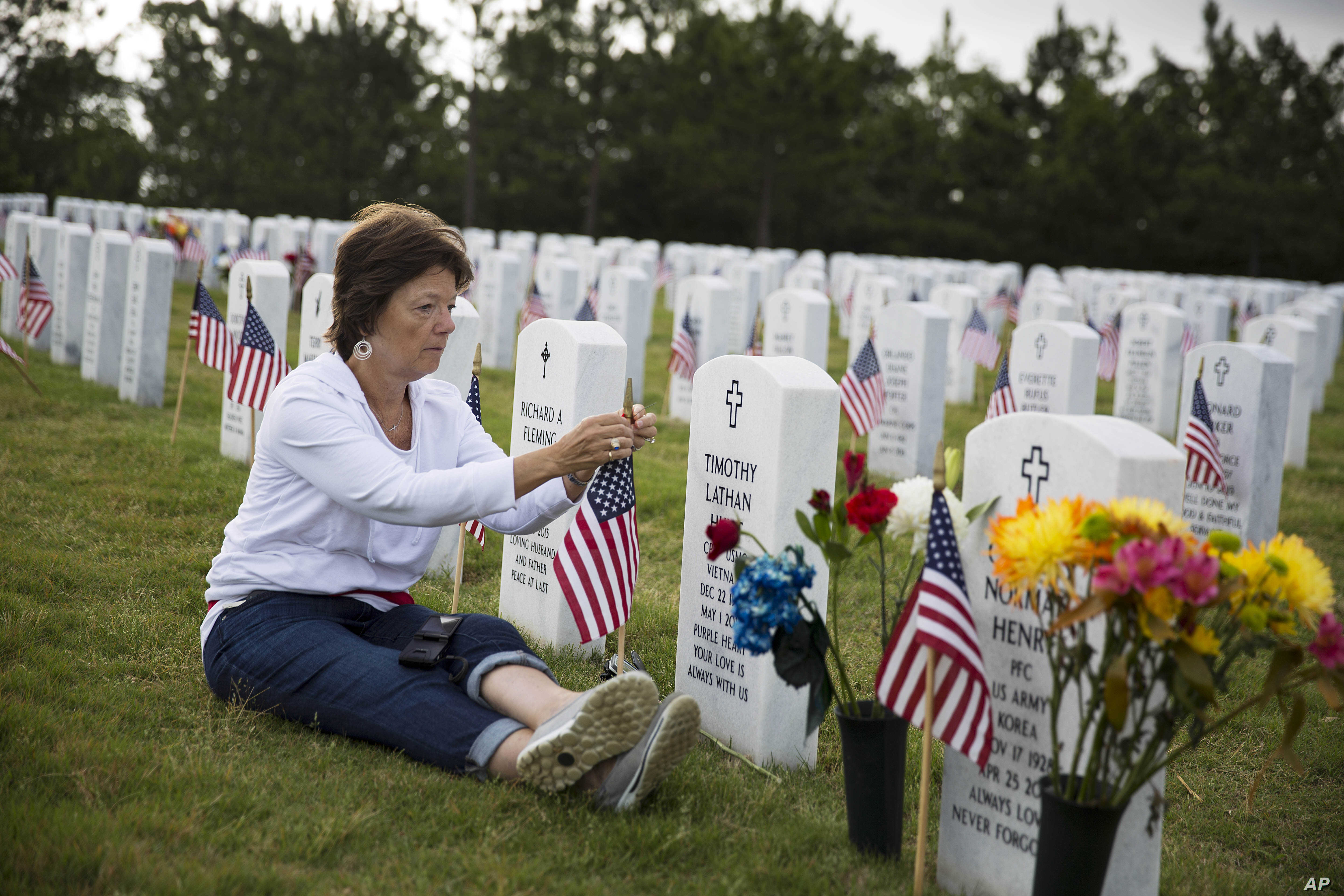 Vickie Hunt sits next to the grave of her late husband, Vietnam veteran Cpl. Timothy Hunt, at Georgia National Cemetery on Memorial Day, Monday, May 25, 2015, in Canton, Ga.