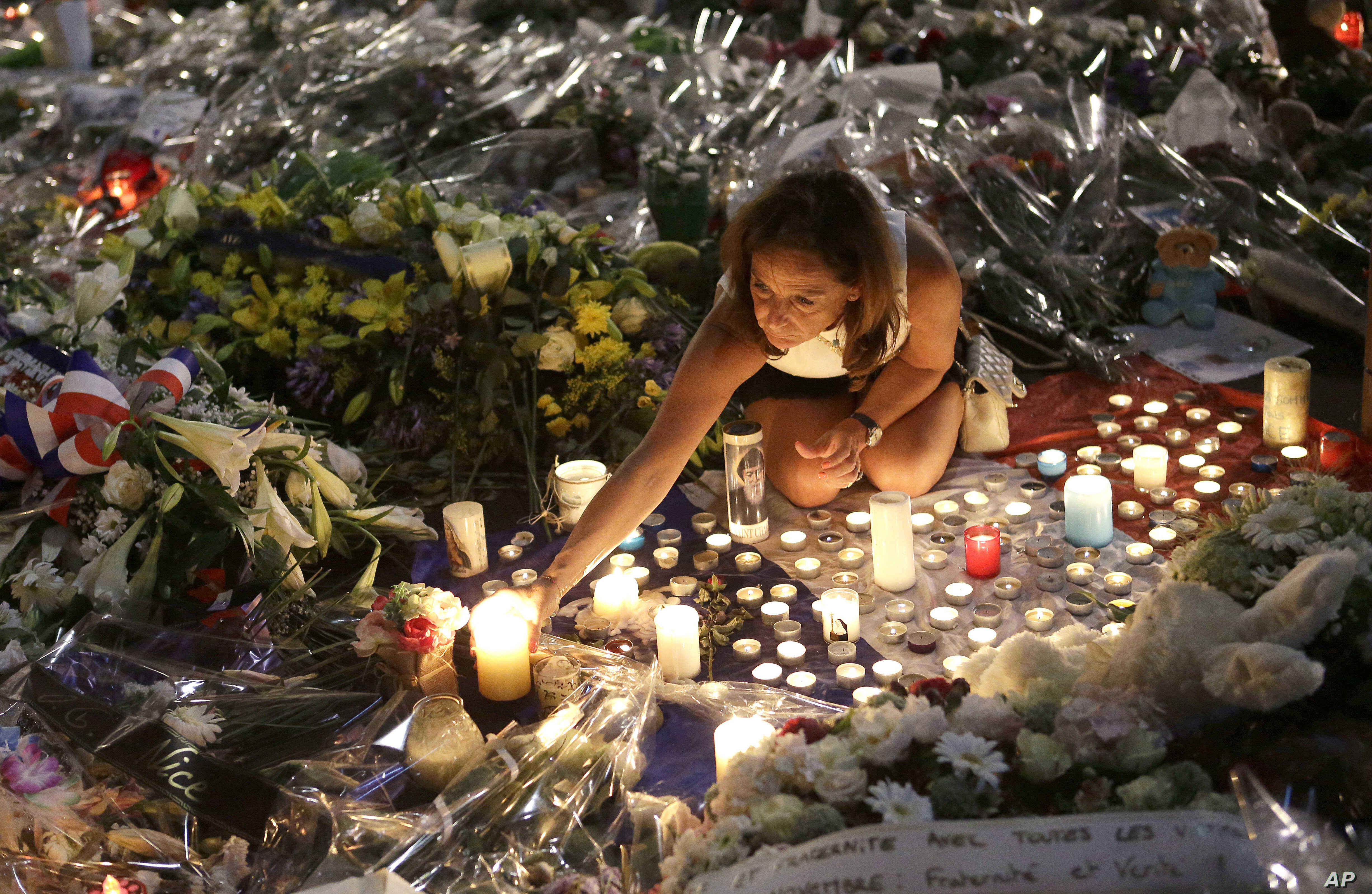 A woman lights candles at a new memorial in a gazebo in a seaside park on the famed Promenade des Anglais in Nice, southern France, July 18, 2016.