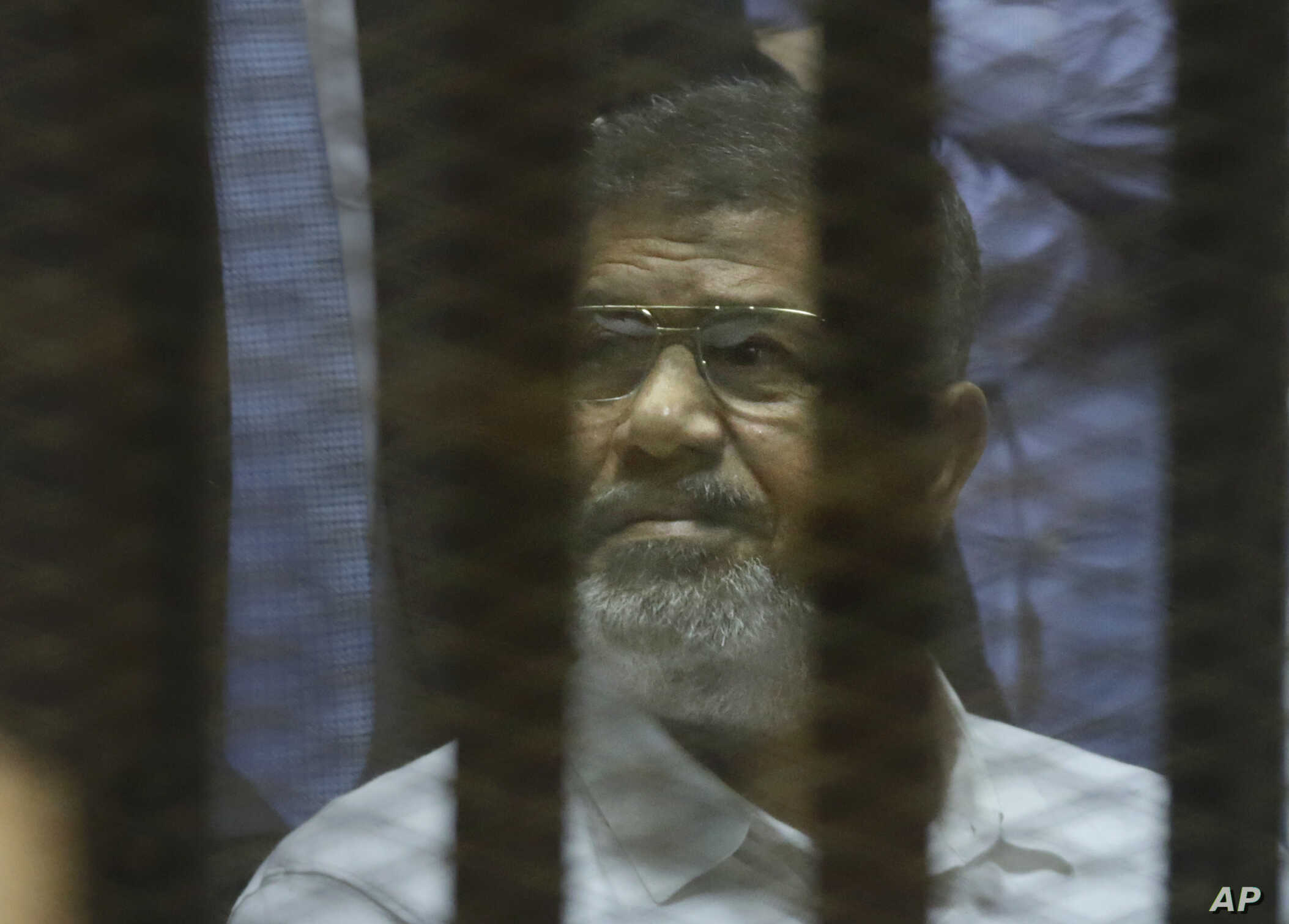 Egypt's ousted Islamist President Mohammed Morsi sits in a soundproof glass cage inside a makeshift courtroom at Egypt's national police academy in Cairo, Egypt, April 21, 2015.