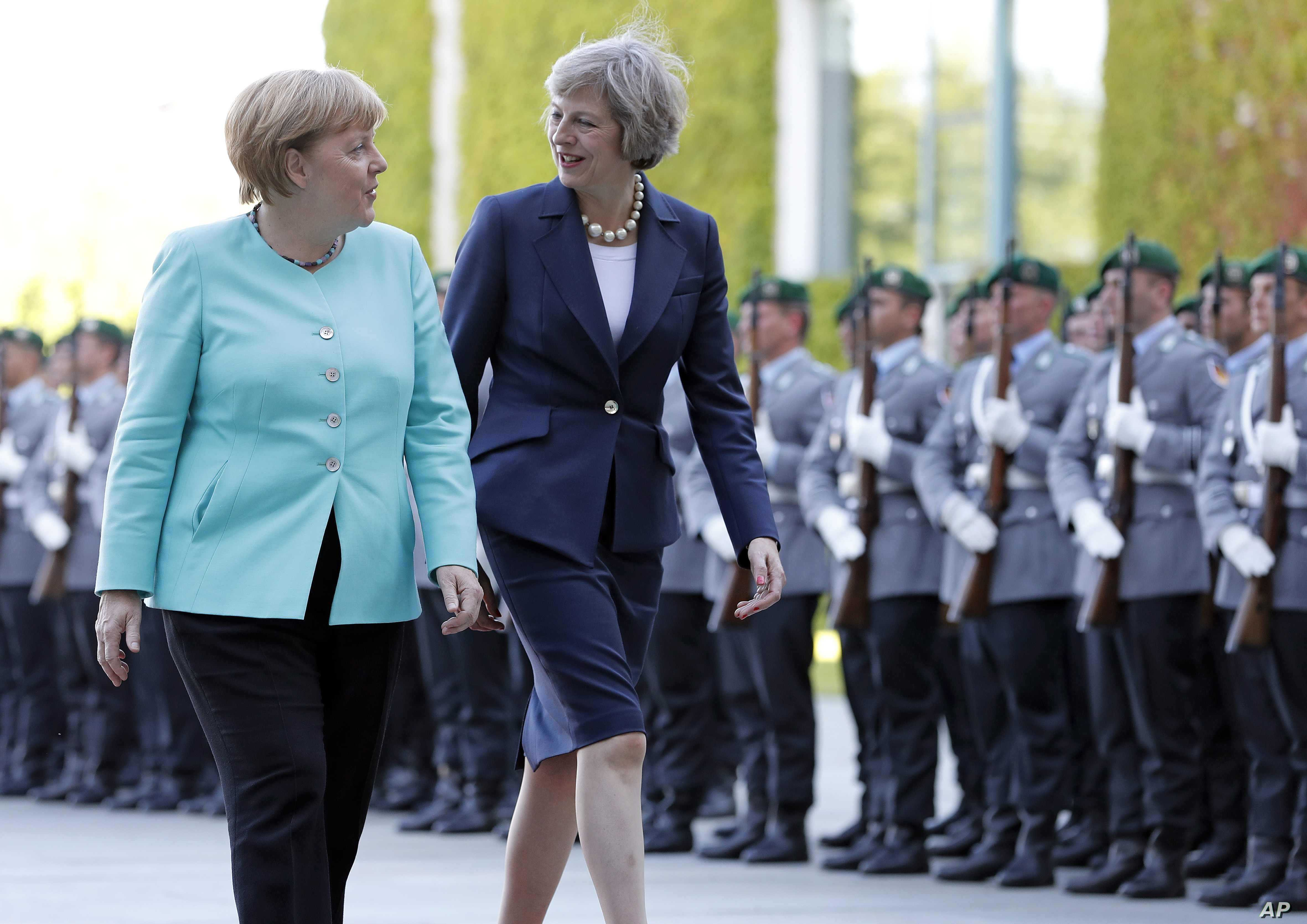 German Chancellor Angela Merkel, left, and British Prime Minister Theresa May walk on the red carpet during a military welcoming ceremony at the chancellery in Berlin Wednesday, July 20, 2016, on May's first foreign trip after being named British Pri...