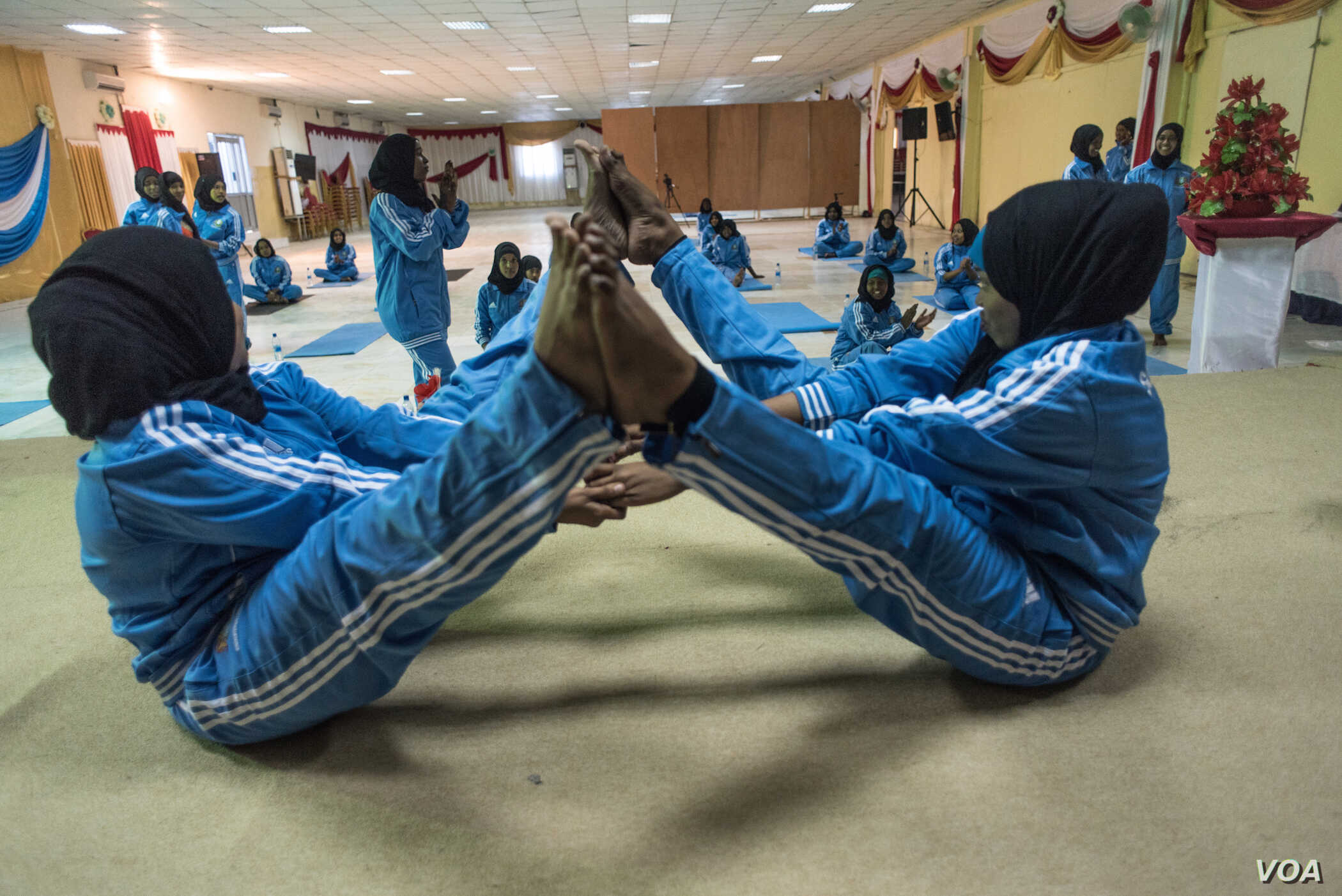 Two women practice a pose during a mind-body wellness program for survivors of trauma in Mogadishu, Somalia, Jan. 16, 2017. (J. Patinkin/VOA)