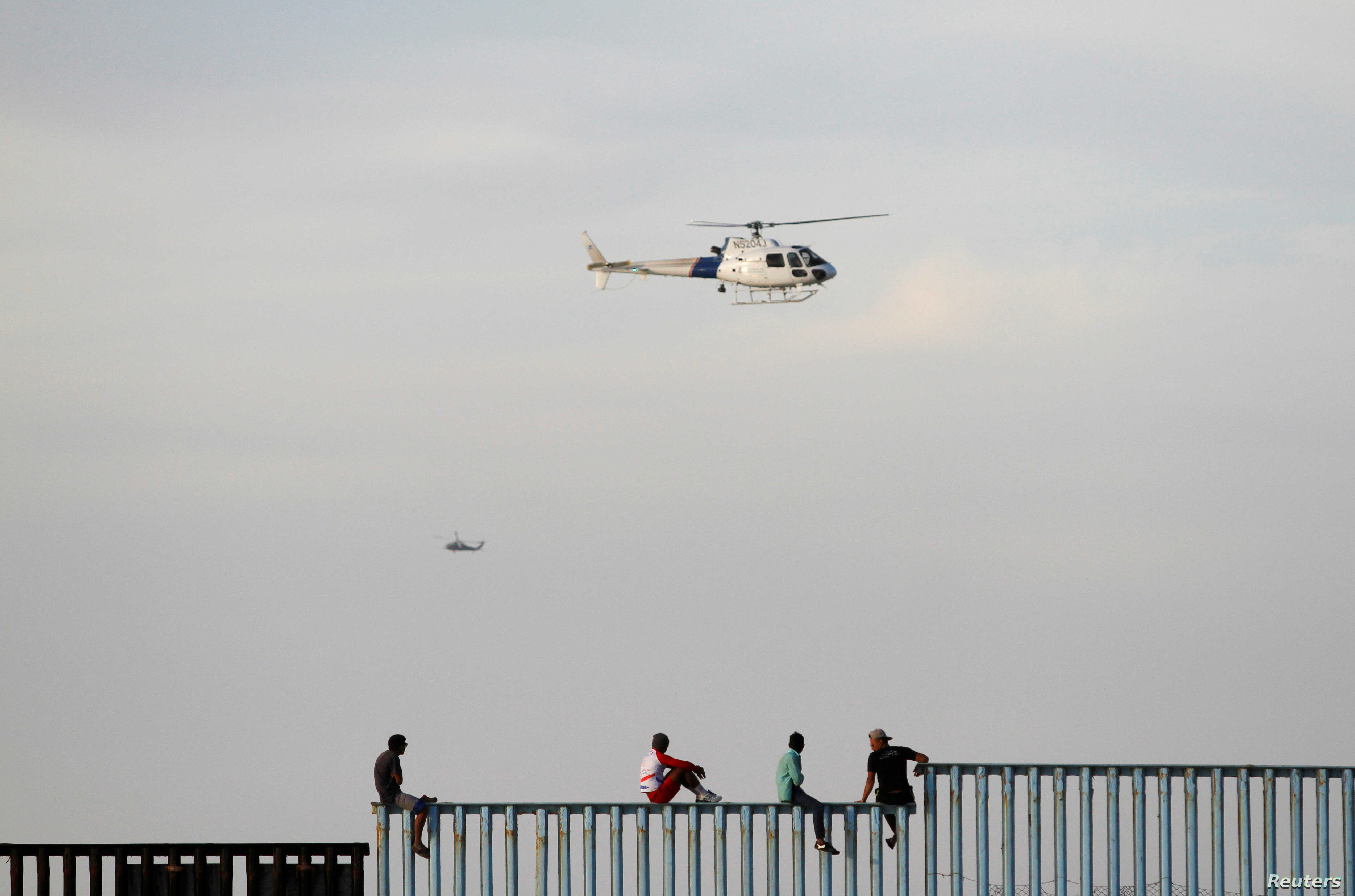 Migrants, part of a caravan of thousands trying to reach the U.S., sit on top of the border fence between Mexico and the United States, after arriving in Tijuana, Mexico, Nov. 13, 2018.