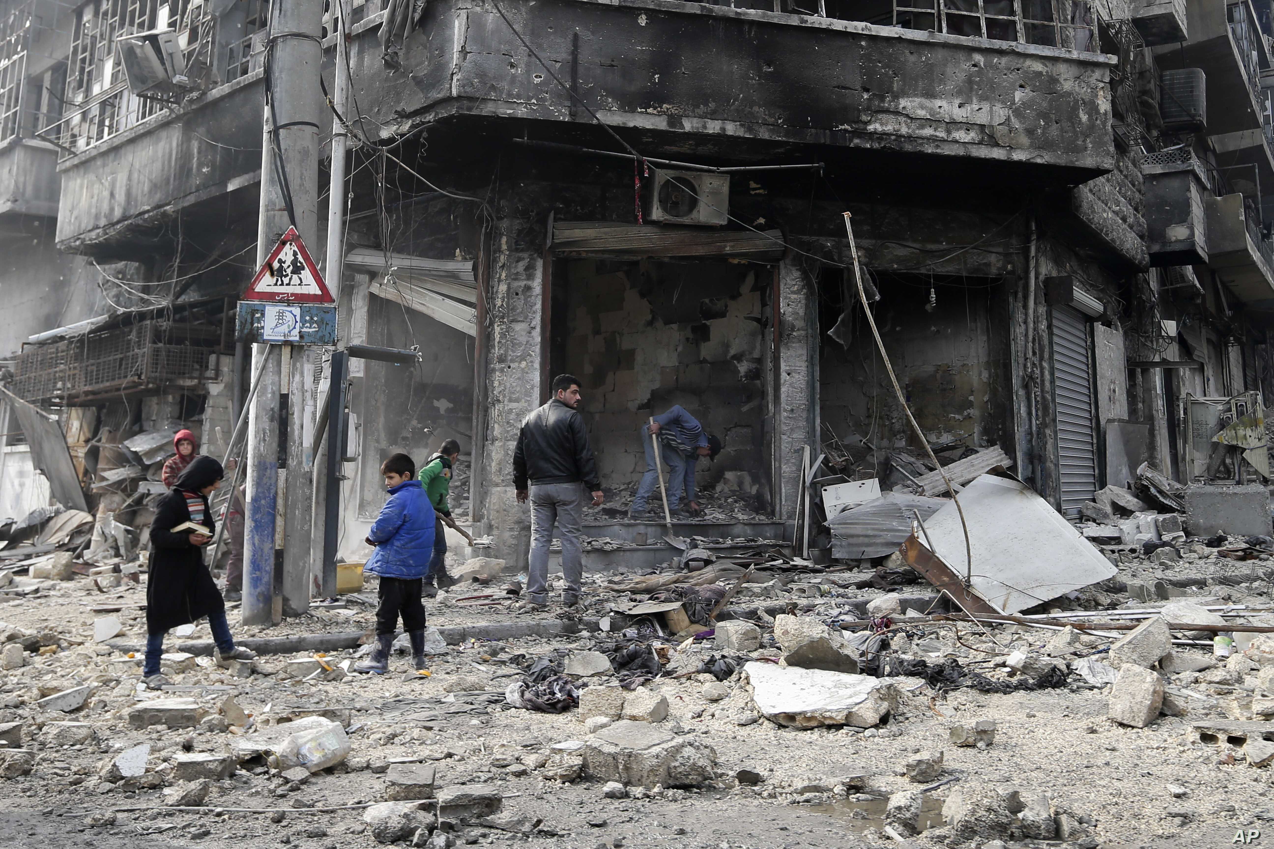 FILE - Syrian children remove rubble in the once rebel-held Bustan al-Qasr neighborhood in eastern Aleppo, Syria. Aleppo, Syria's largest city, was widely brought to ruin by years of war, and now with Russia and Turkey leading peace efforts, intern...