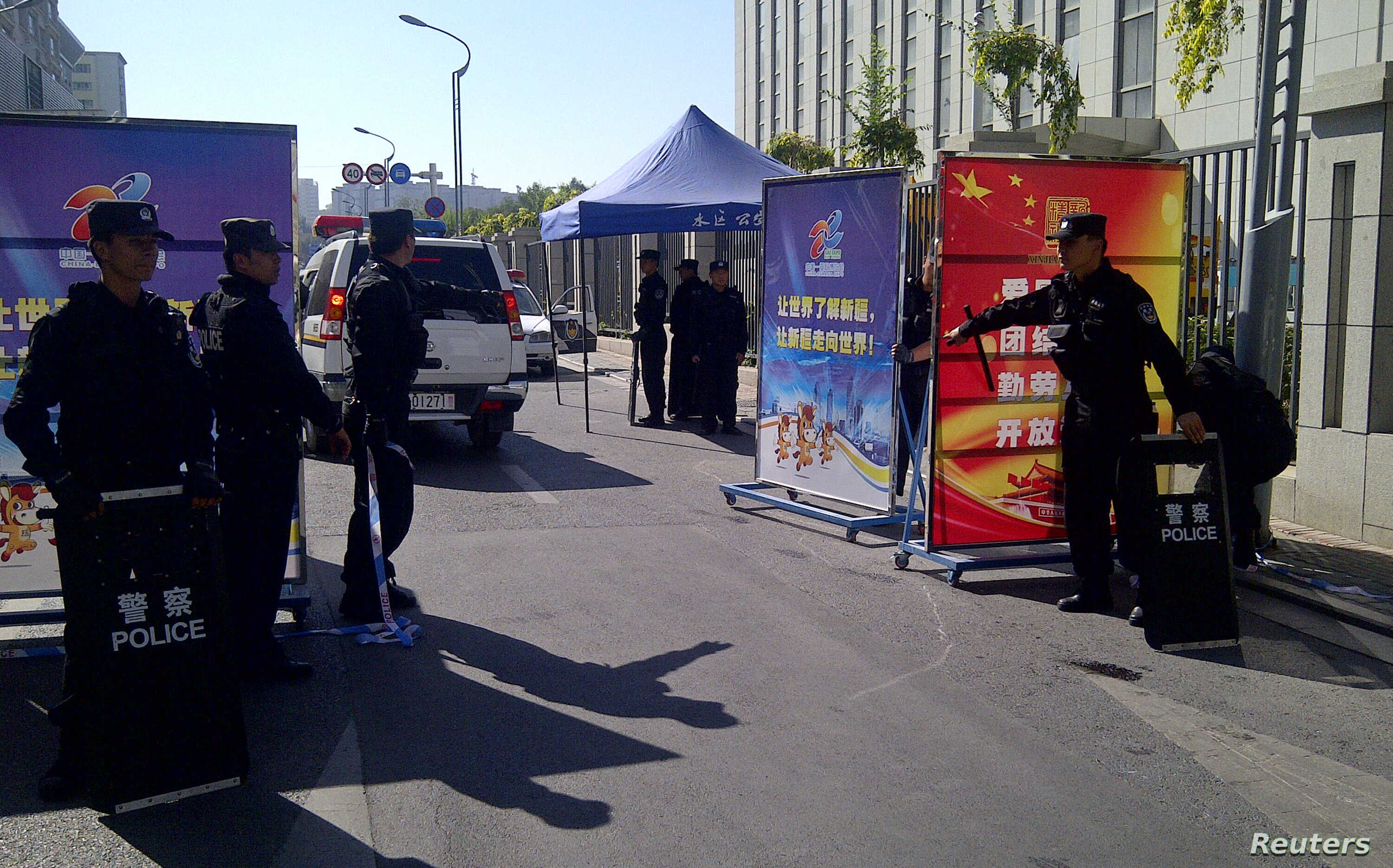 Police with riot gear guard a checkpoint on a road near a courthouse where ethnic Uighur academic Ilham Tohti's trial is taking place in Urumqi, Xinjiang Uighur Autonomous Region, Sept. 17, 2014.