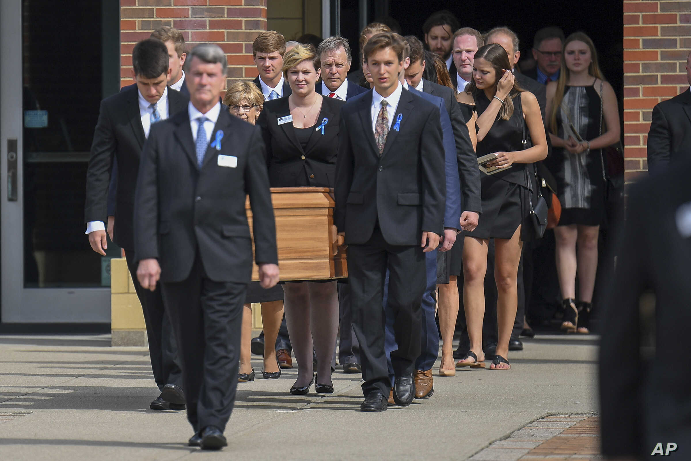 The casket of Otto Warmbier is carried from Wyoming High School after his funeral, June 22, 2017.