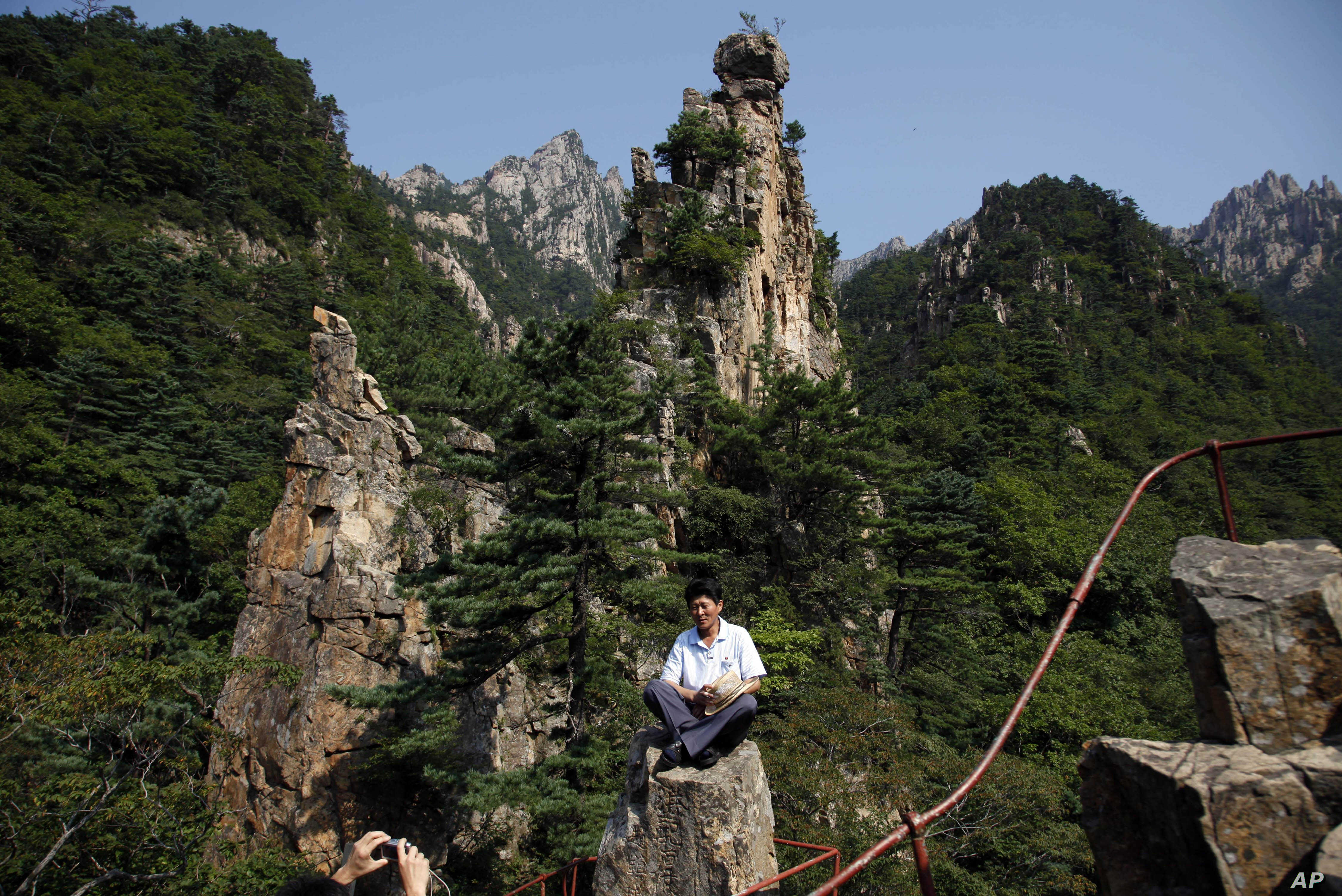 FILE - A North Korean guide poses for photos among the peaks of the Mount Kumgang resort, also known as Diamond Mountain, in North Korea, Sept. 1, 2011. South Korea's Moon Jae-in is look at ways to build relations with North Korea, including resuming...