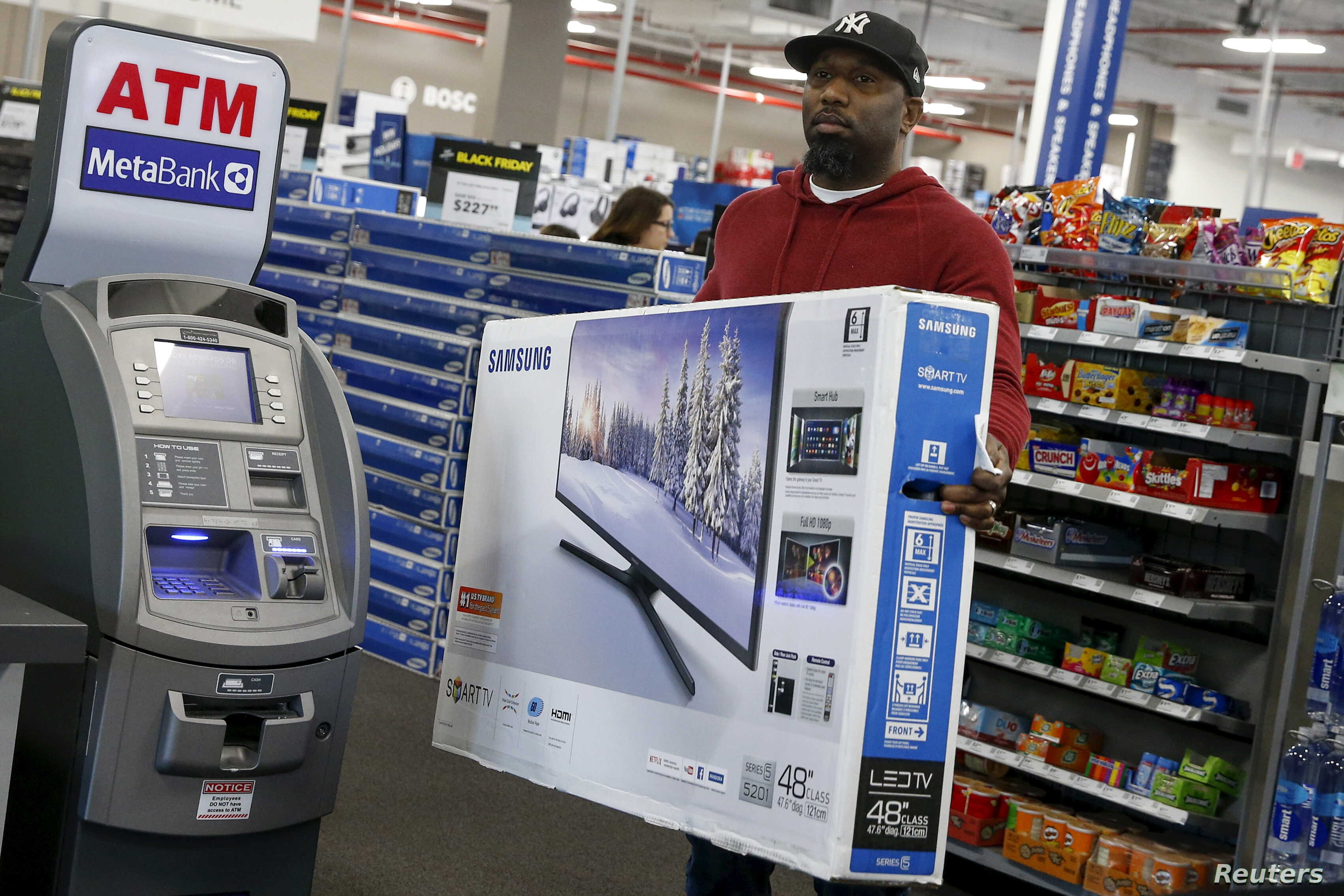 FILE - A shopper carries a Samsung television at a Best Buy store in Westbury, New York. Nov.  27, 2015.