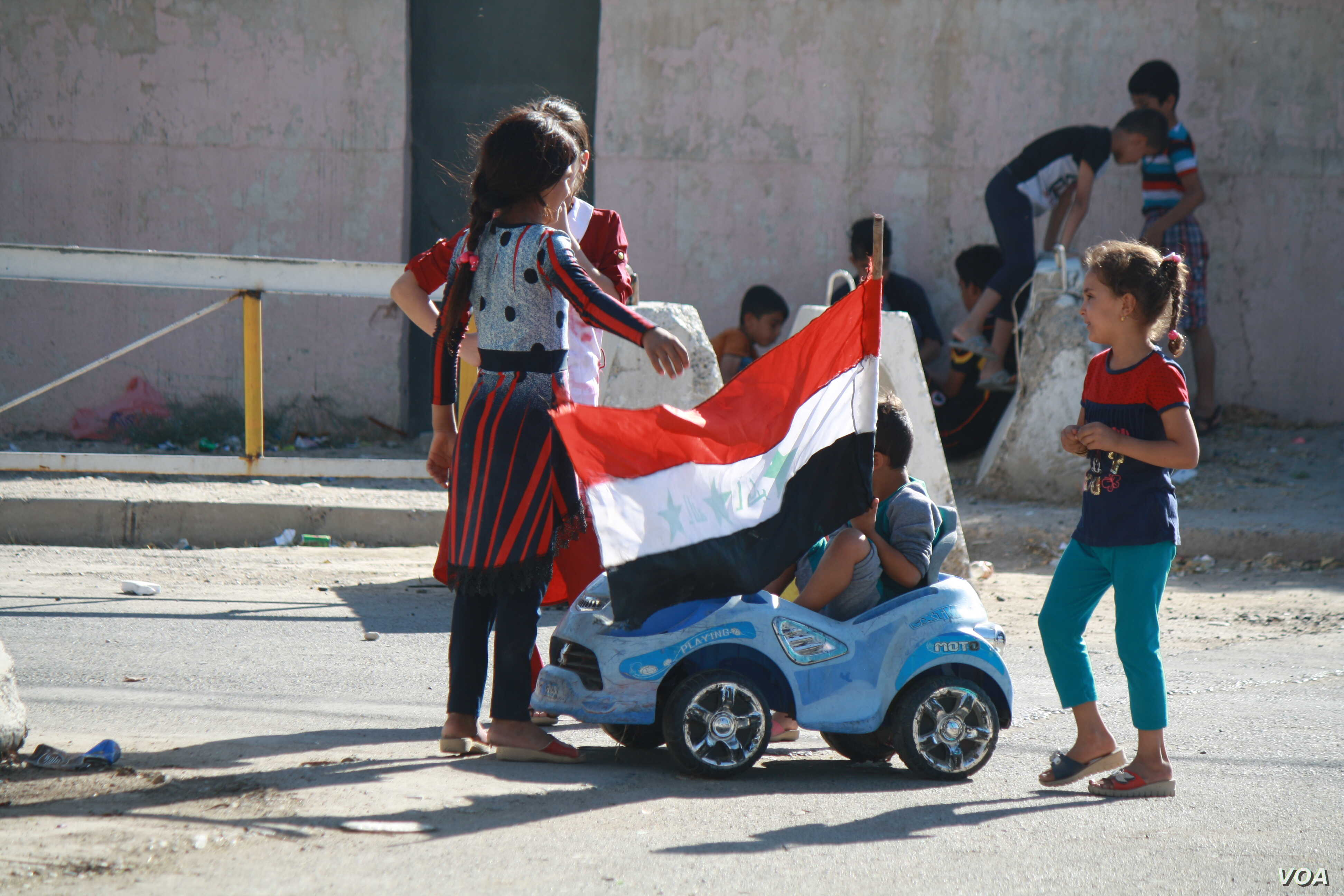 Children play with an Iraqi flag after Baghdad ordered troops were ordered to take Kirkuk from Kurdish forces on Oct. 17, 2017 in Kirkuk, Iraq. (H.Murdock/VOA)