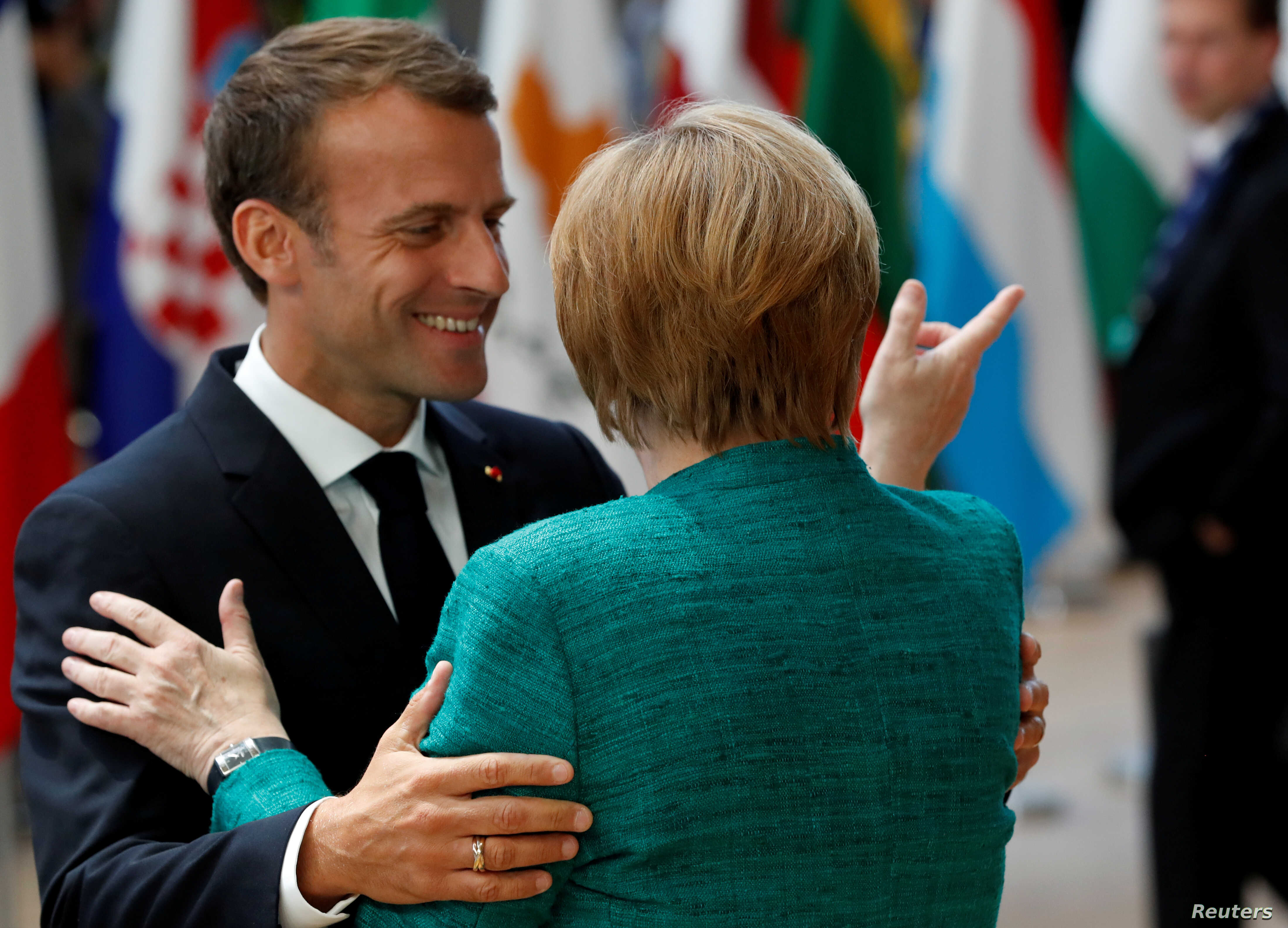 German Chancellor Angela Merkel and French President Emmanuel Macron greet each other as they arrive at an European Union leaders summit in Brussels, June 28, 2018.