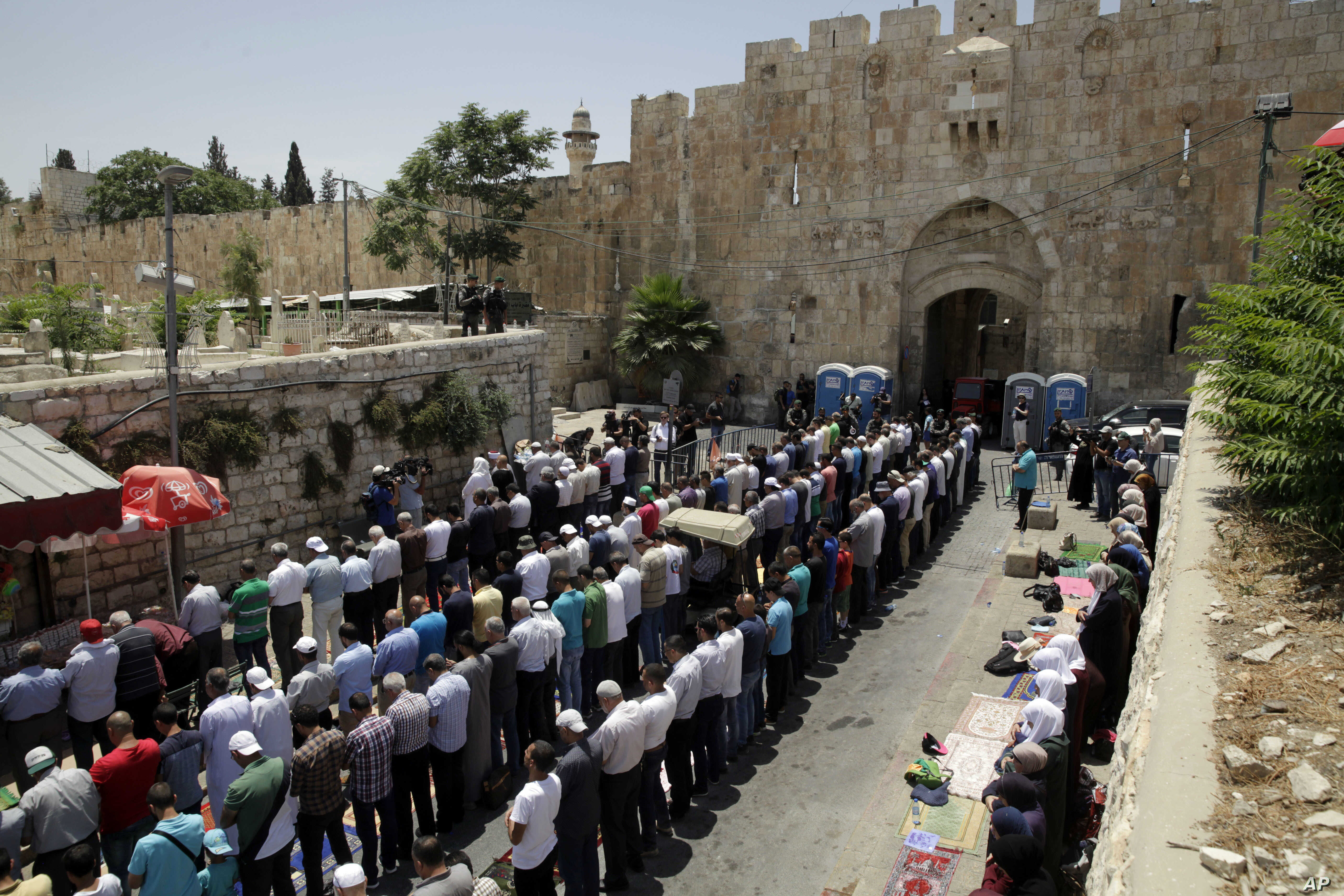 Palestinians pray outside the Lion's Gate in Jerusalem's Old City, Tuesday, July 18, 2017. A dispute over metal detectors has escalated into a new showdown between Israel and the Muslim world over a contested Jerusalem shrine that has been at the cen...