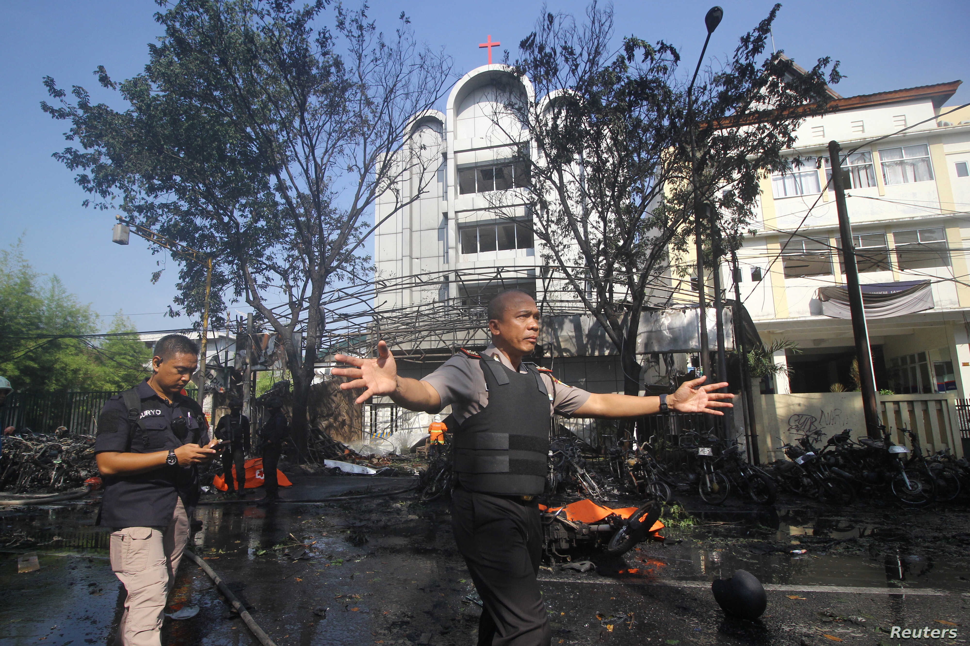 Police stand guard near the site of a blast at the Pentecost Church Central Surabaya, in Surabaya, East Java, Indonesia, May 13, 2018.