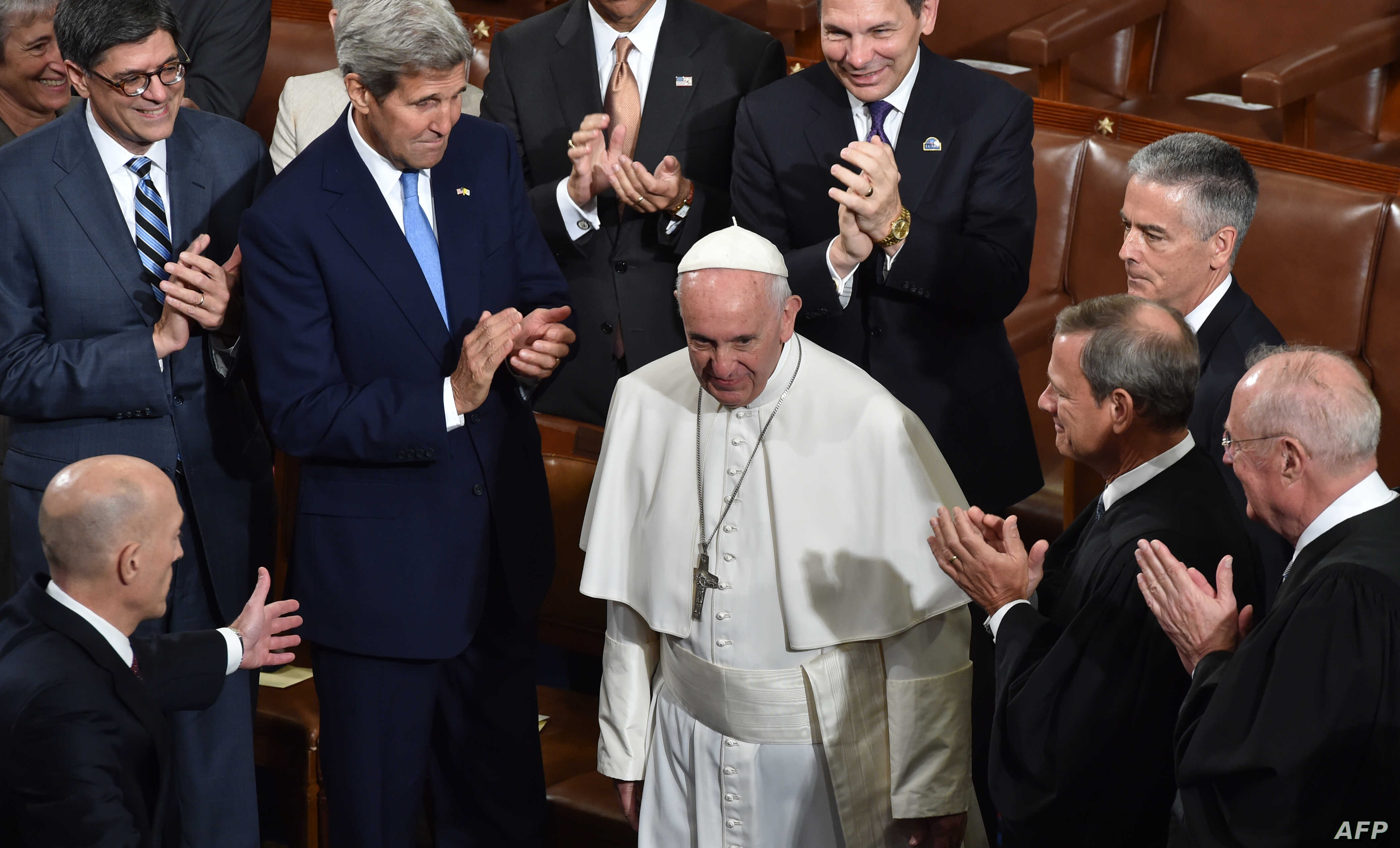 US Secretary of Stae John Kerry(2nd R),Treasury Secretary Jacob Lew (L)justices of the US Supreme Court and other cabinet members applaud as Pope Francis arrives to address the joint session of Congress on September 24, 2014 in Washington, DC.