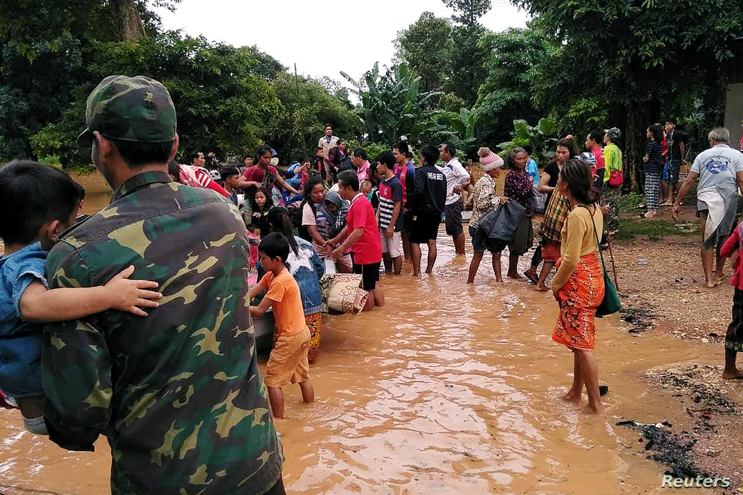 Villagers carry their belongings as they evacuate after the Xepian-Xe Nam Noy hydropower dam collapsed in Attapeu province, Laos, July 24, 2018.