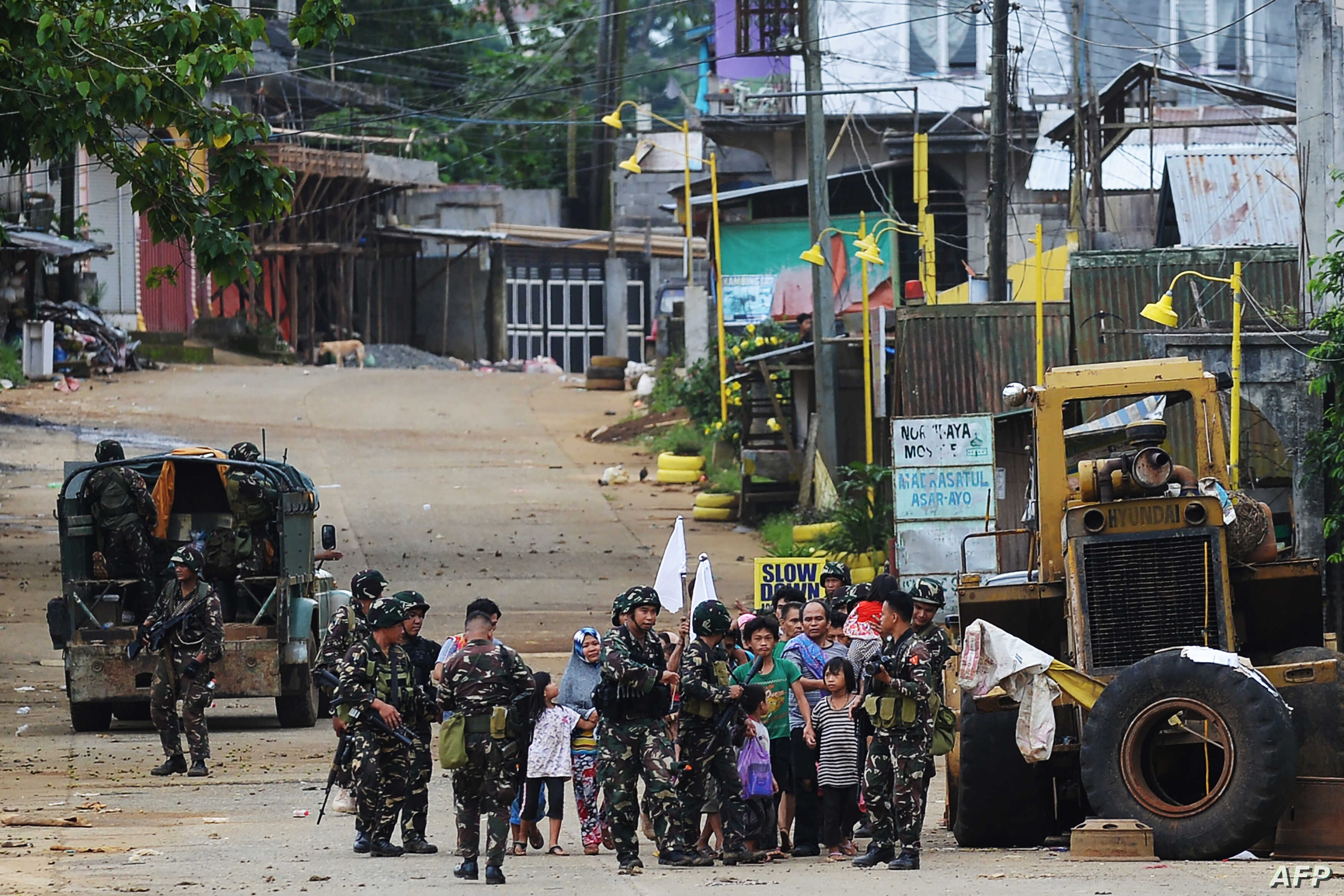 Philippine troops escort civilians, as a military truck covers them from sniper fire, in a village on the outskirts of Marawi on the southern island of Mindanao, May 31, 2017, as fighting between government forces and Islamist militants continues.
