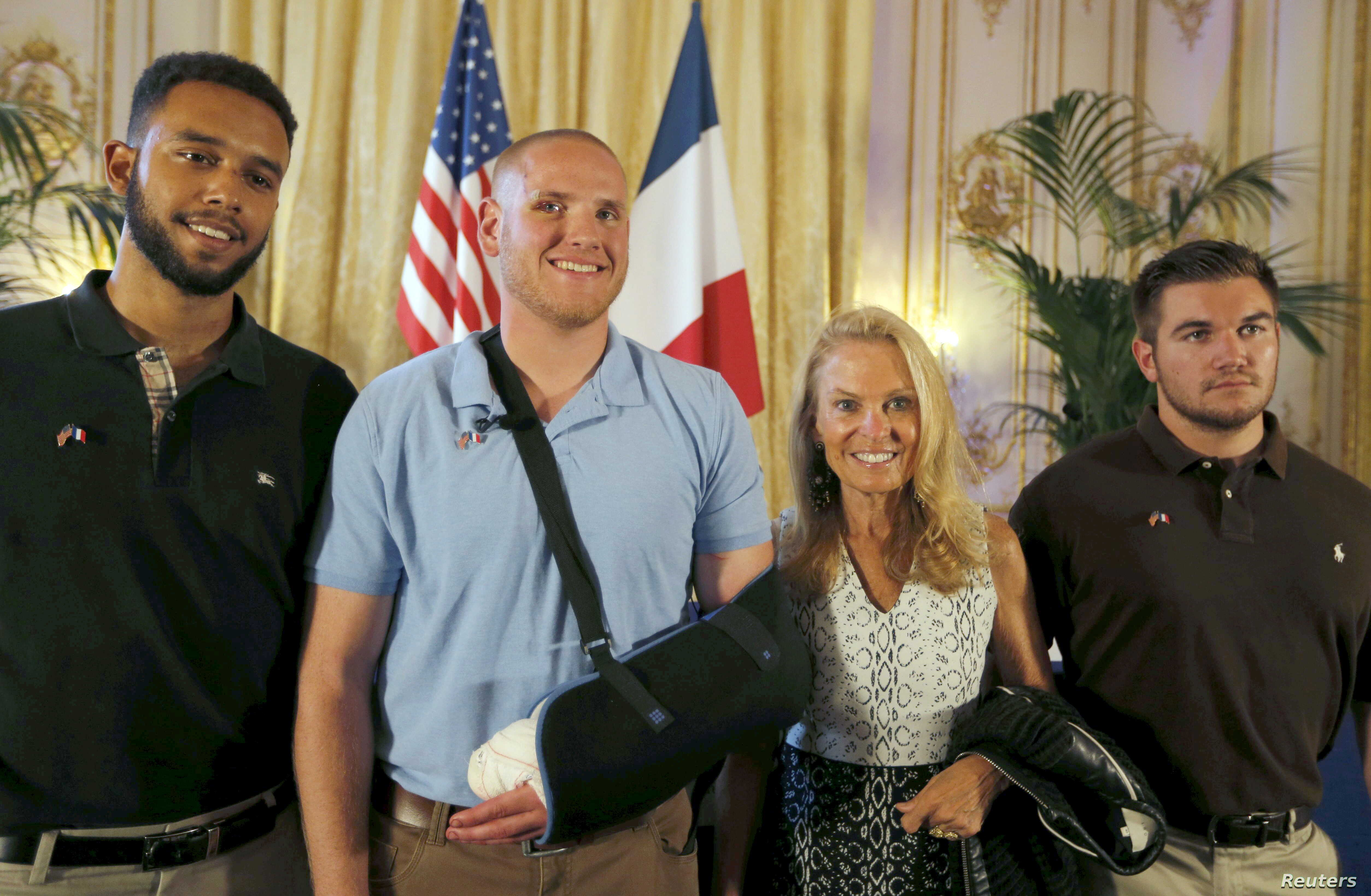 U.S. ambassador to France Jane Hartley (2nd R) presents student Anthony Sadler (L), U.S Airman First Class Spencer Stone (2nd L) and National Guardsman Alek Skarlatos (R) as they attend a ceremony at the U.S. Embassy in Paris, France, Aug. 23, 2015.