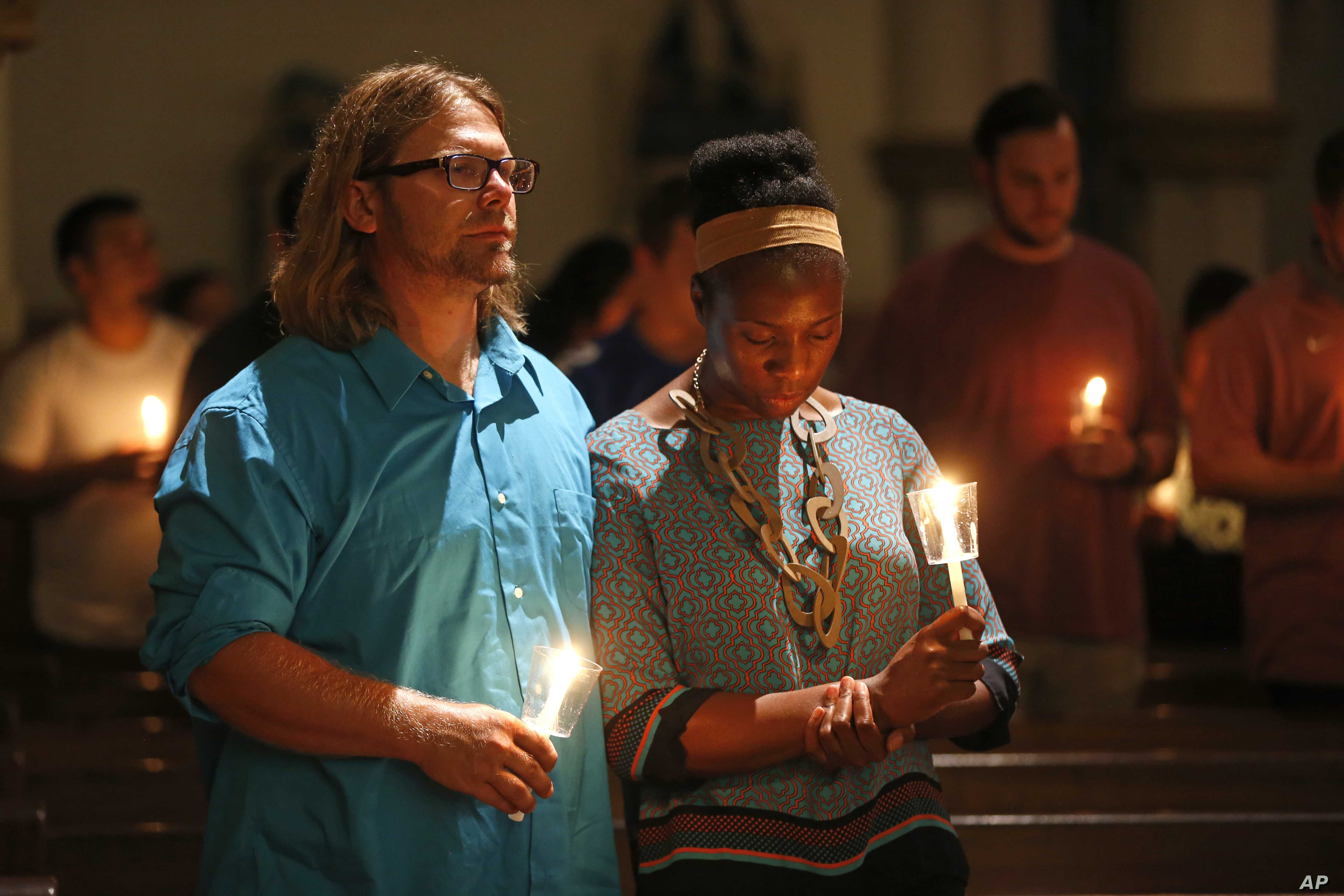Lily Reagan and Kenneth McCarroll pray at Cathedral Guadalupe in Dallas, in honor of the police officers slain Thursday.