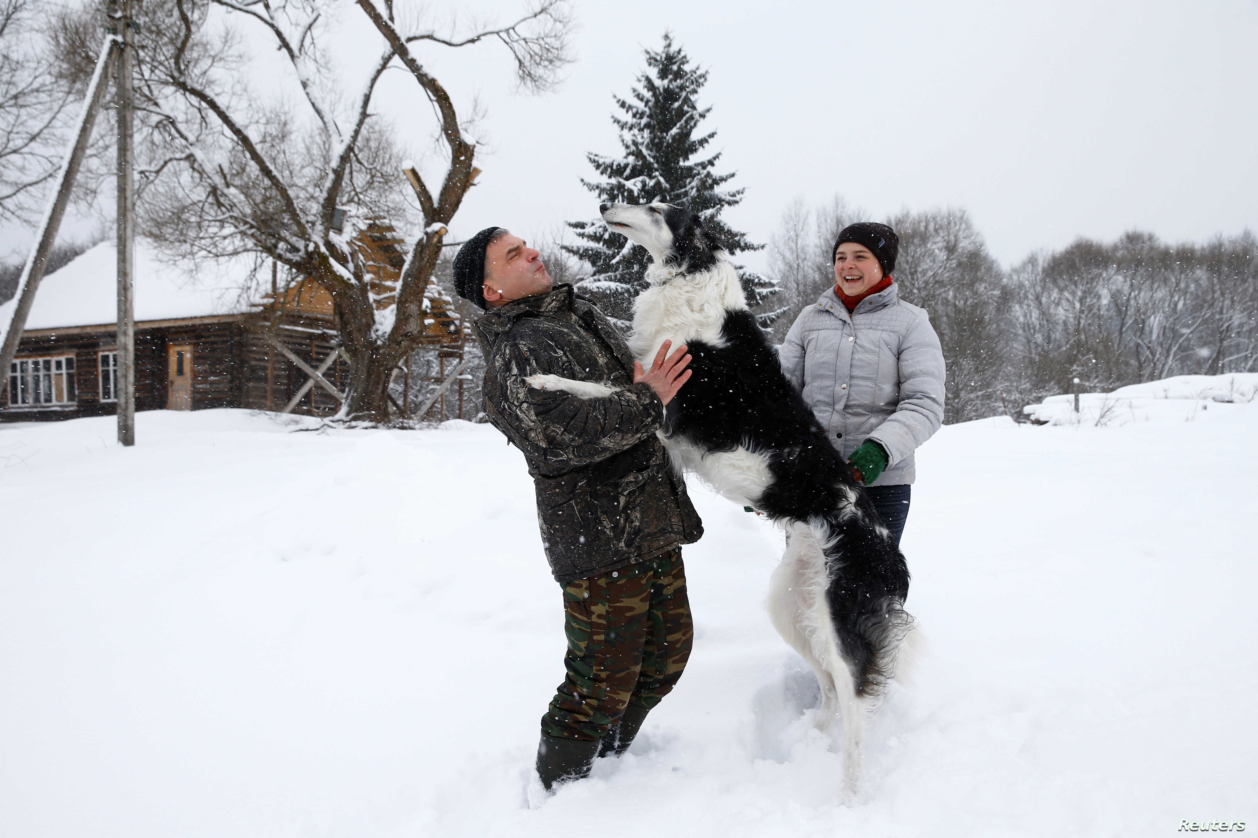 """Dmitry Shamovich and his wife, Anastasia Kuzmenkova, play with the dog Amur at their homestead Zaimka Leshego in the village of Sosnovy Bor, Belarus, Feb. 7, 2018. """"Four years ago I was here, at the homestead for the first time — we arrived with ot..."""