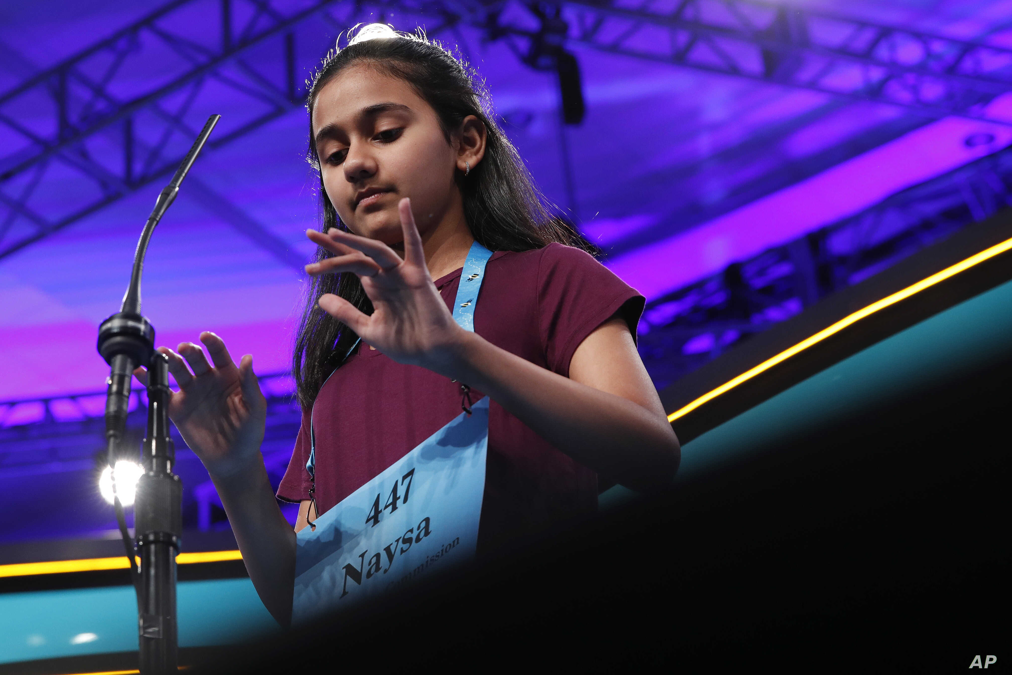 Naysa Modi, 12, from Frisco, Texas, types her word in the air while spelling correctly during the evening finals of the Scripps National Spelling Bee in Oxon Hill, Md., May 31, 2018.